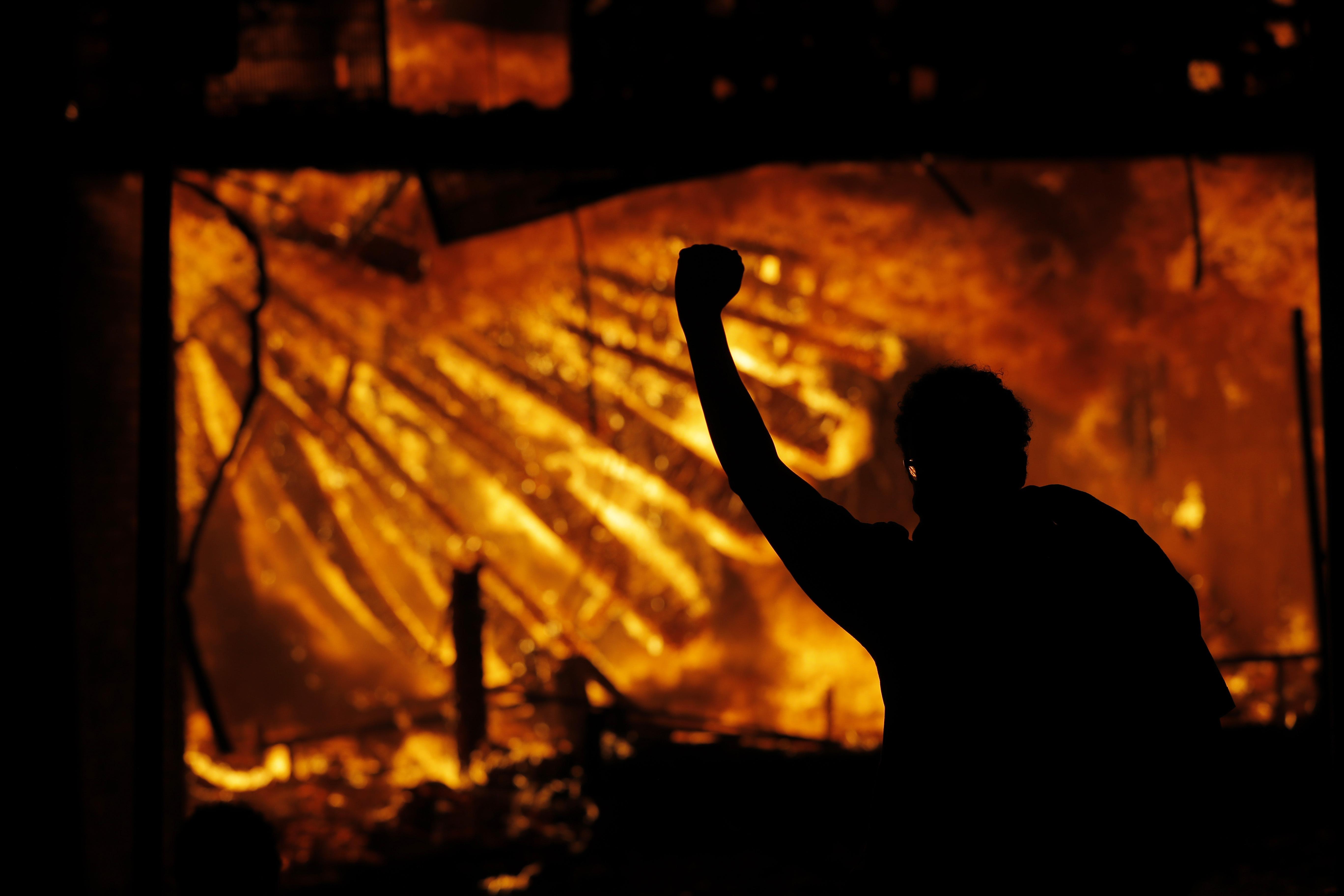 Un manifestante hace un ademán frente al edificio en llamas del Tercer Precinto del Departamento de Policía de Minneapolis el jueves 28 de mayo de 2020 (Foto AP/Julio Cortez)