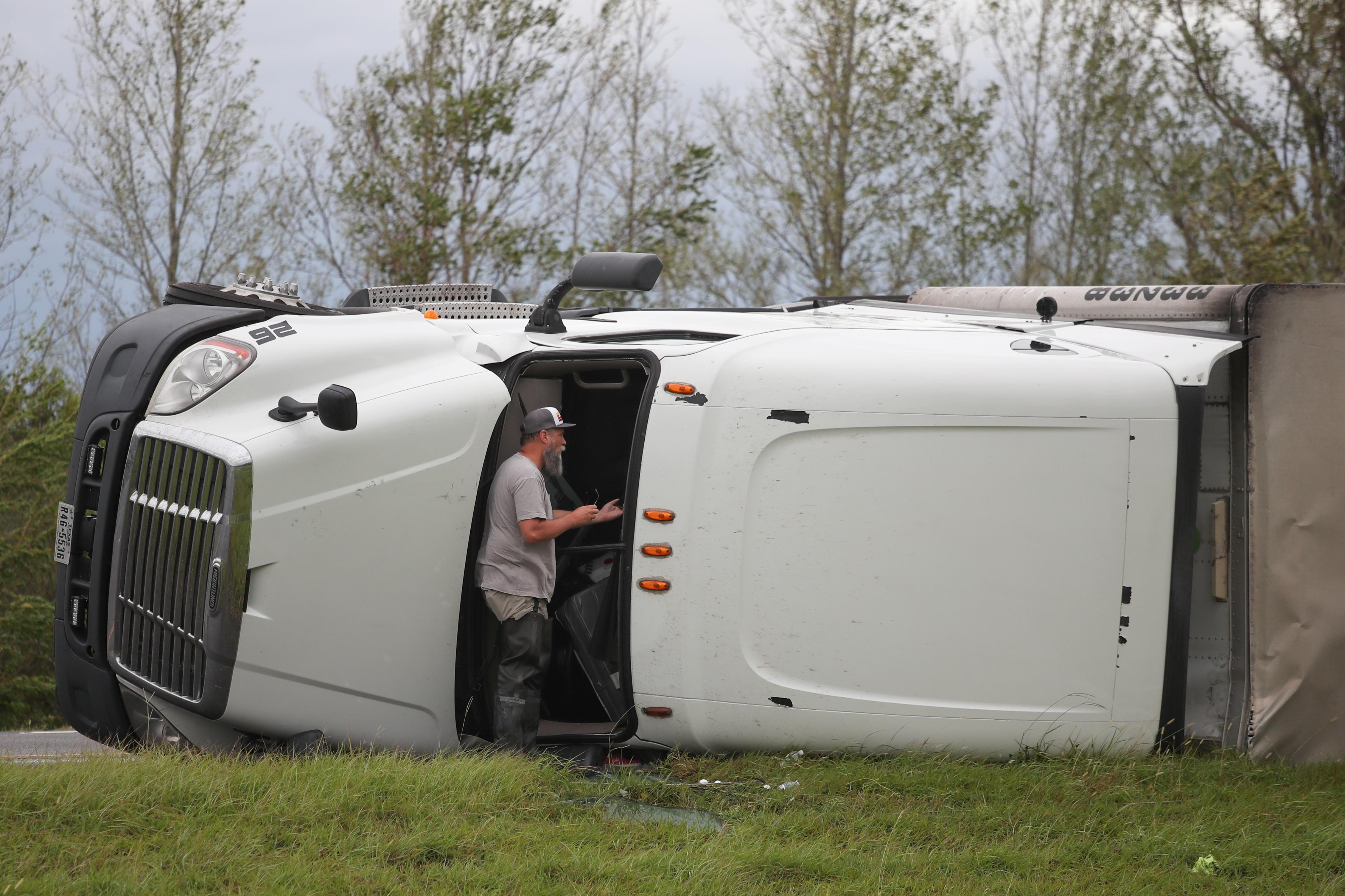 Un transeúnte habla con el conductor de un camión de 18 ruedas volcado después del huracán Laura en la I-10 en Vinton, Luisiana, el 27 de agosto de 2020 (REUTERS/Adrees Latif)