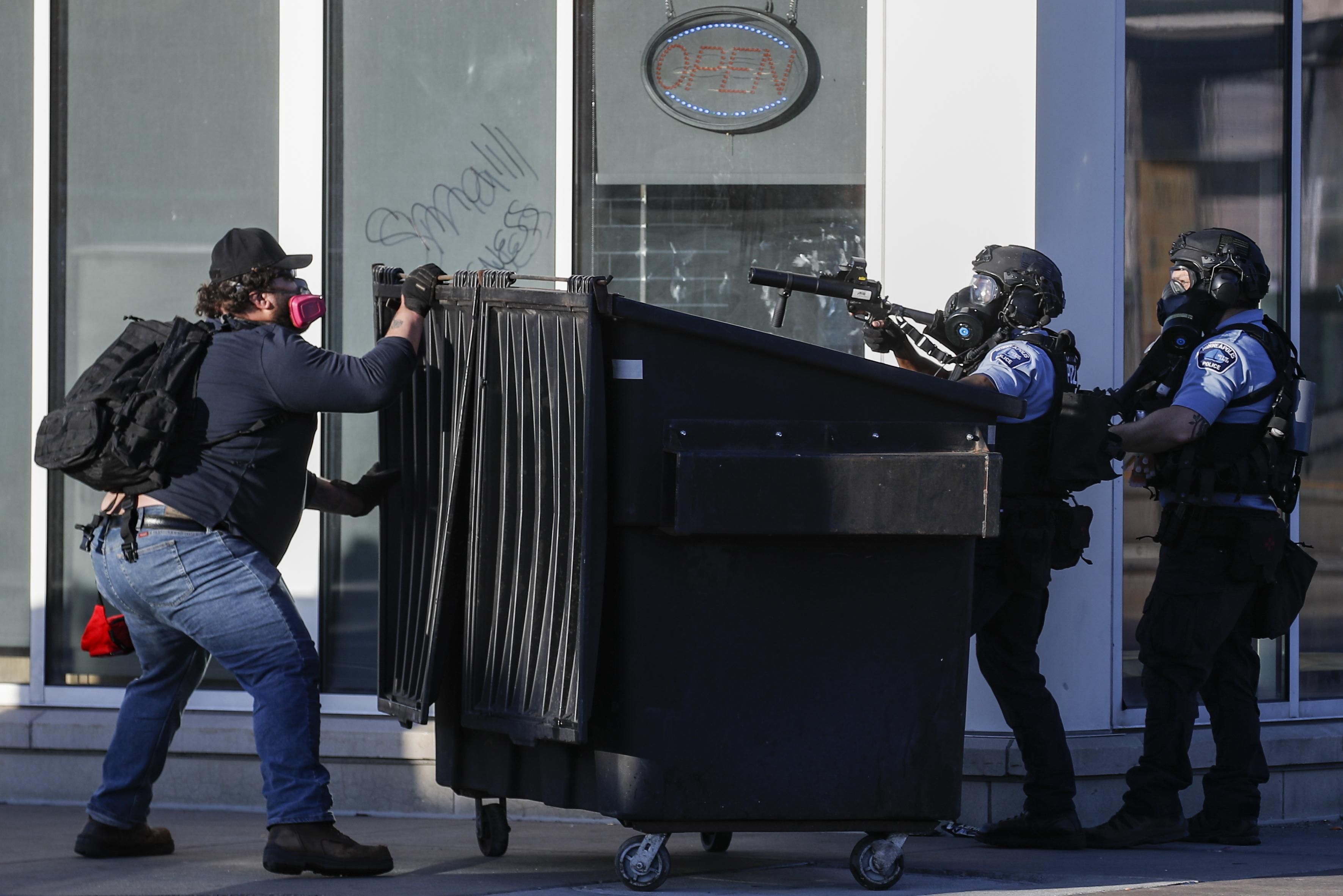 Un hombre se enfrenta a dos policías que usan munición menos letal en sus armas, el jueves 28 de mayo de 2020, en St. Paul, Minnesota (Foto AP/John Minchillo)