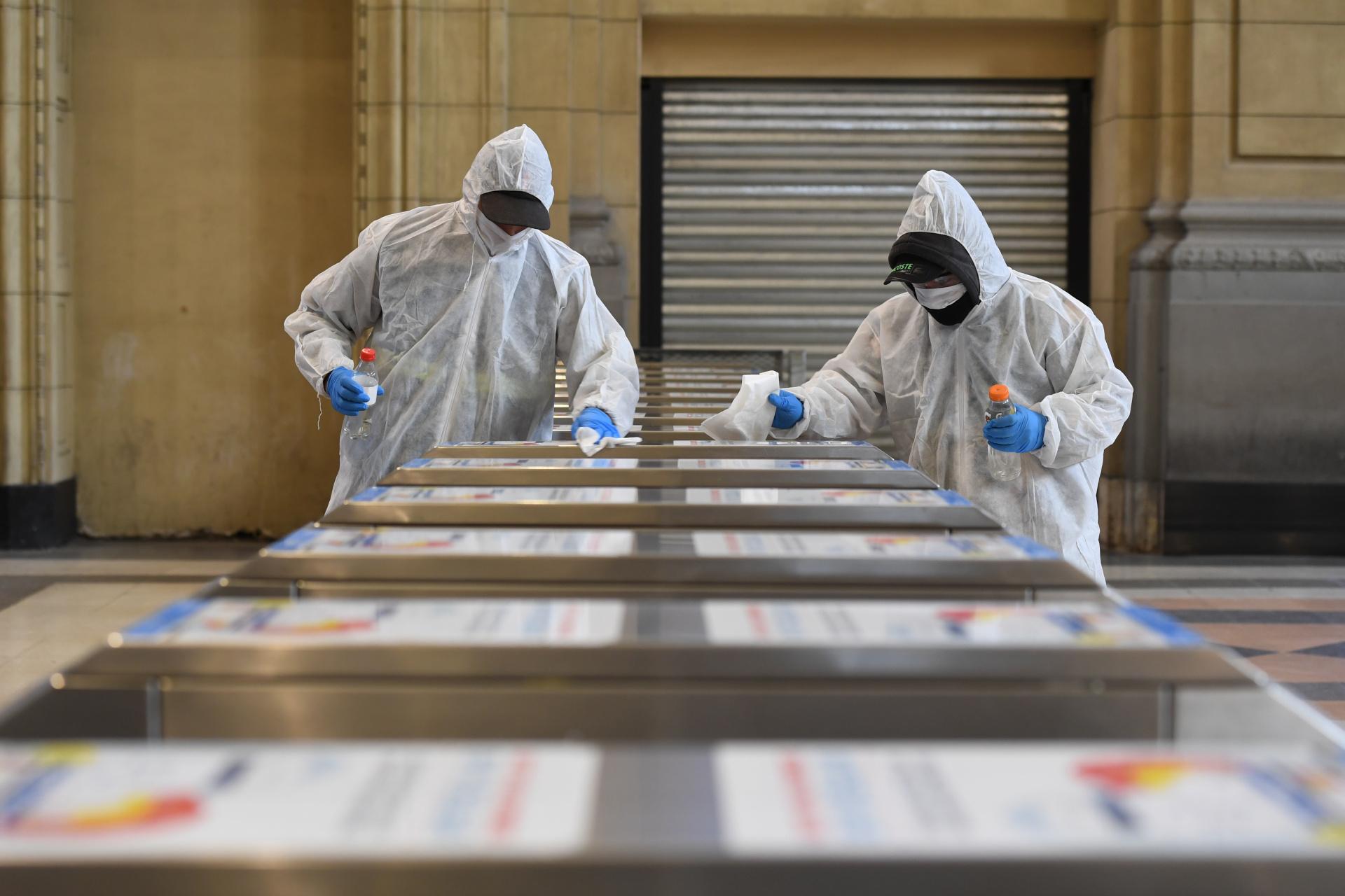 Dos trabajadores, con su uniforme correspondiente y elementos de protección, desinfectan los molinetes de llegada a la estación Constitución del Tren Roca. La limpieza de las terminales ferroviarias se triplicó durante la pandemia.