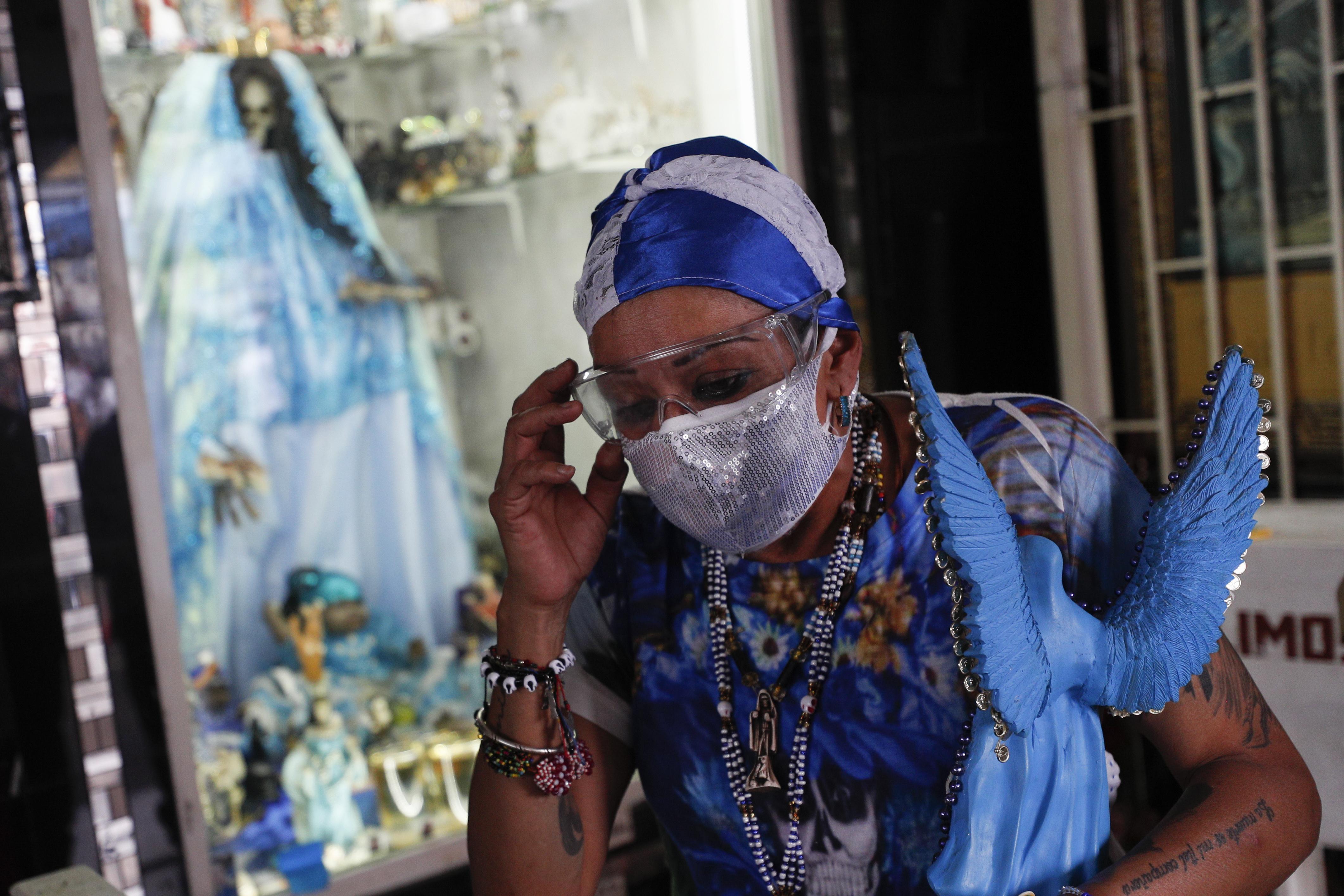 Una mujer se ajusta las gafas protectoras mientras se va después de visitar un altar a la Santa Muerte en el barrio de Tepito de la Ciudad de México, el lunes 1 de junio de 2020. (Foto AP / Rebecca Blackwell)
