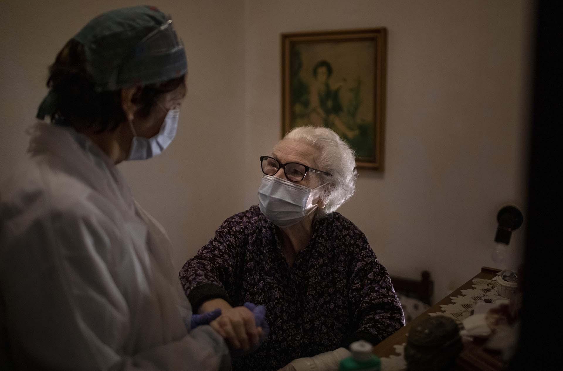 Pepita Jove Puiggros, de 92 años, sostiene la mano de una enfermera durante una visita en Barcelona, España (AP Photo/Emilio Morenatti)
