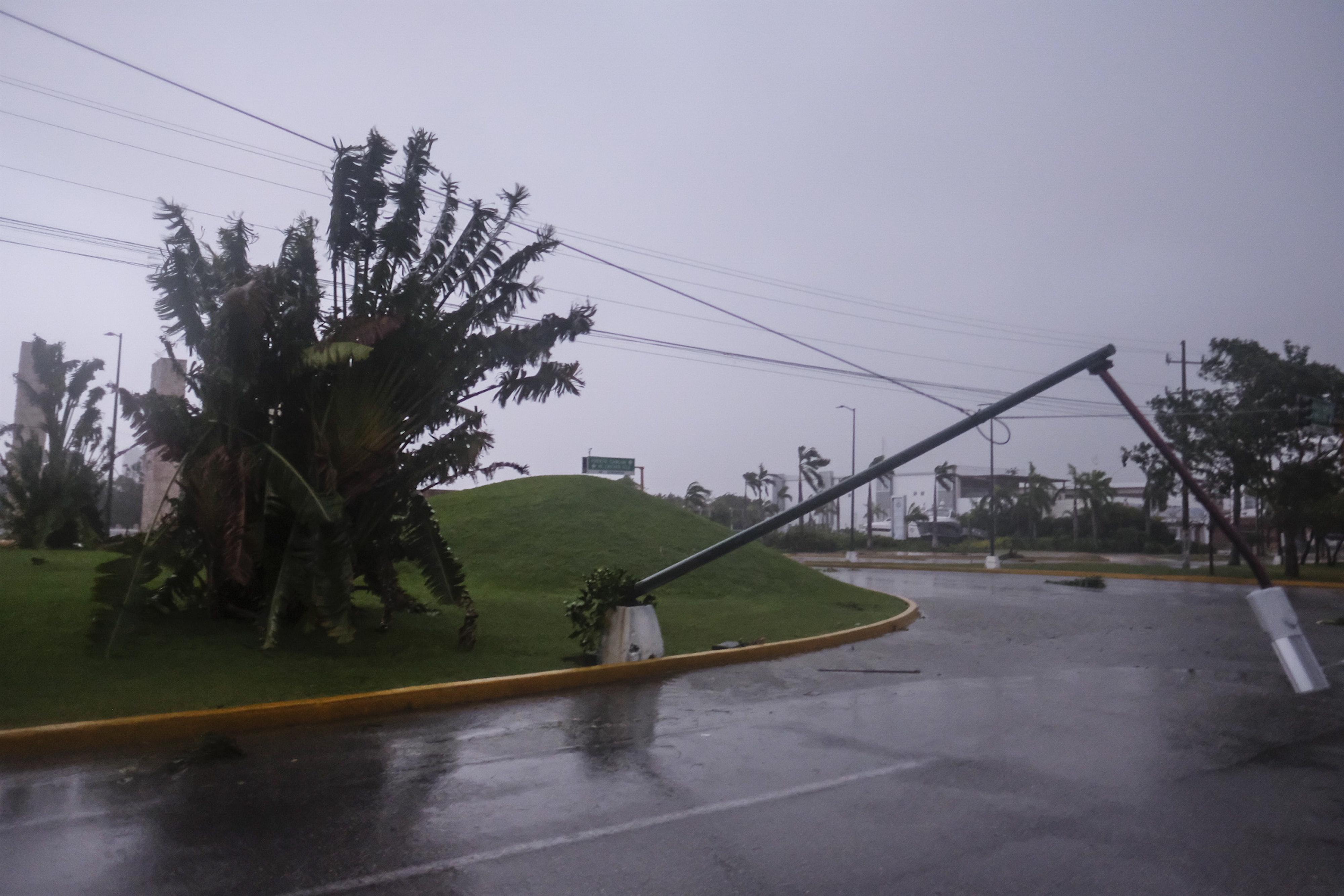 Un poste de luz se inclina sobre una calle después del paso del huracán Delta en Cancún, México, el miércoles 7 de octubre de 2020.