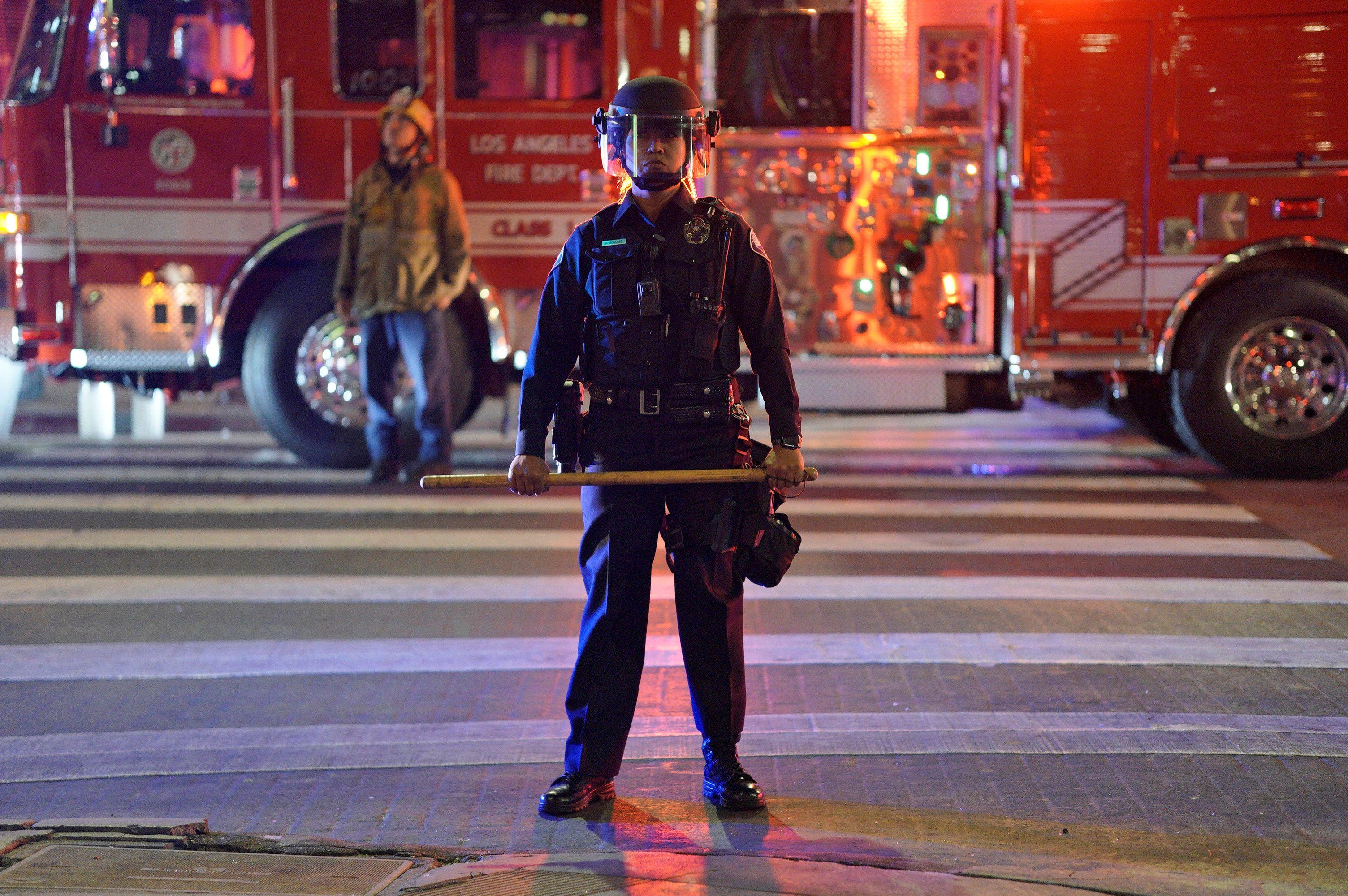Una policía observa a los manifestantes en Los Angeles, California
