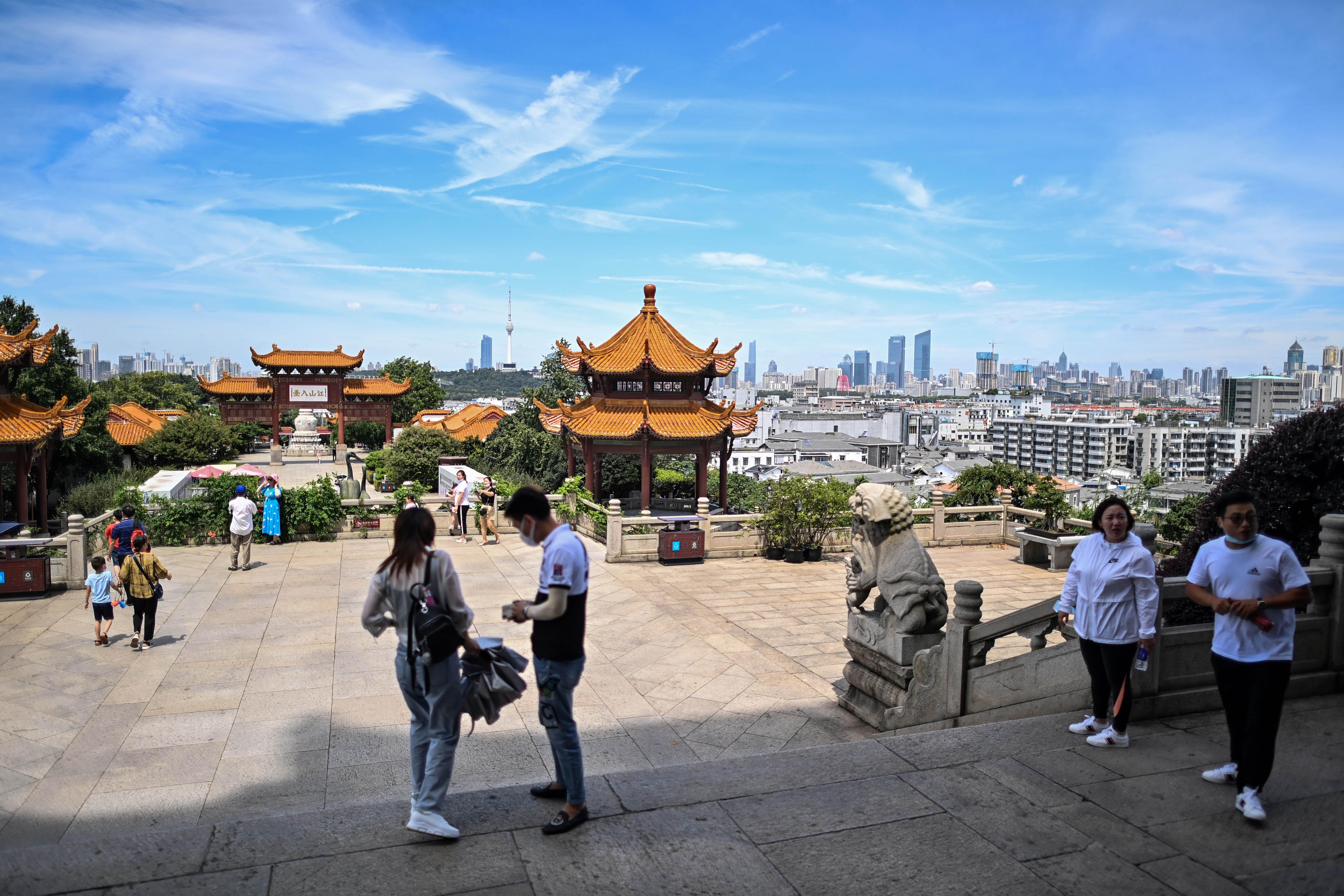 Los turistas volvieron y se fotografían sonrientes frente a la Torre de la Grulla Amarilla, uno de los monumentos emblemáticos de Wuhan, con sus artesanías rojas y naranjas
