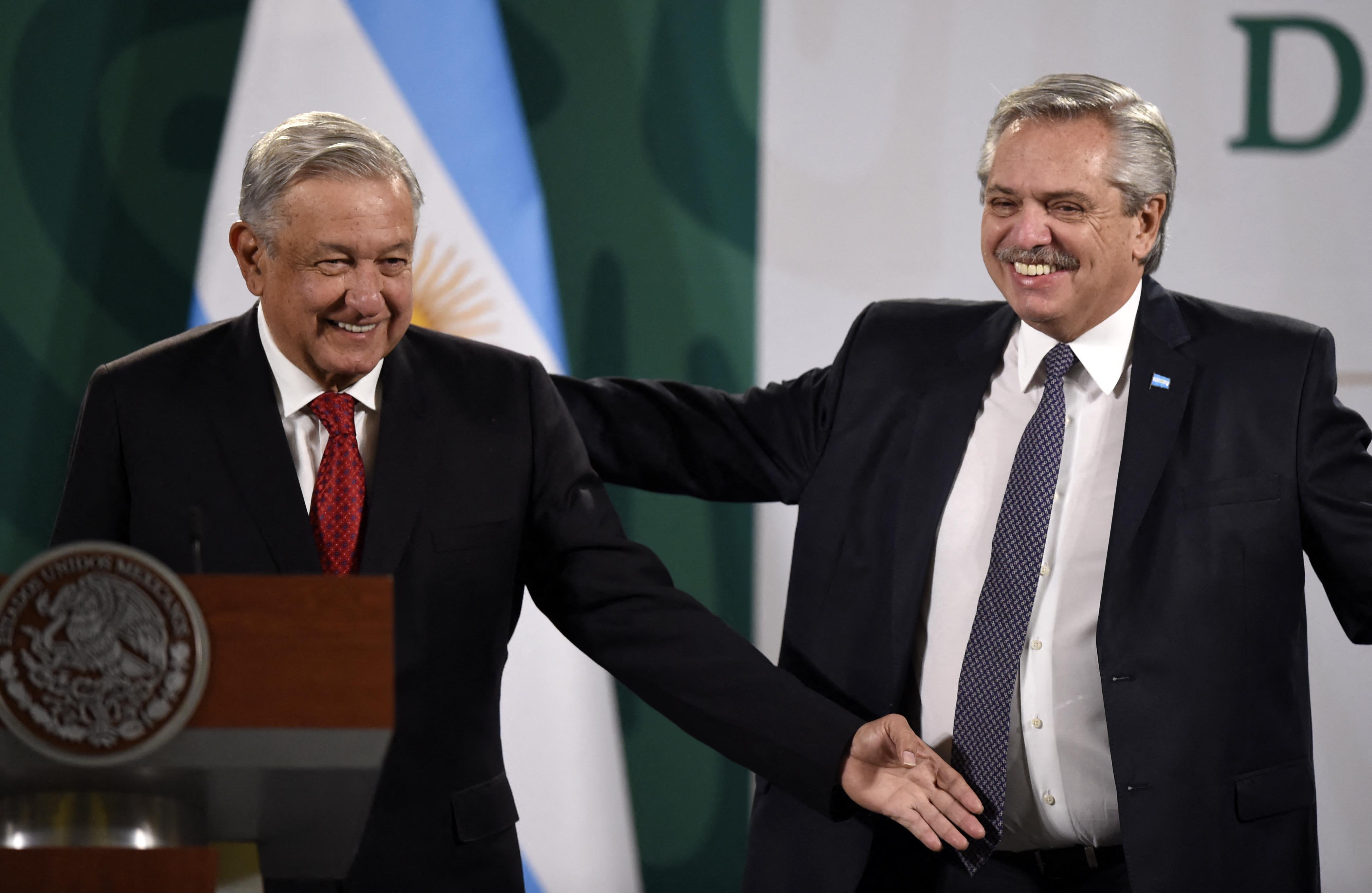 El presidente mexicano, Andrés Manuel López Obrador y su homólogo argentino, Alberto Fernández, hacen un gesto mientras se preparan para ofrecer una conferencia de prensa conjunta en la Ciudad de México el 23 de febrero de 2021.