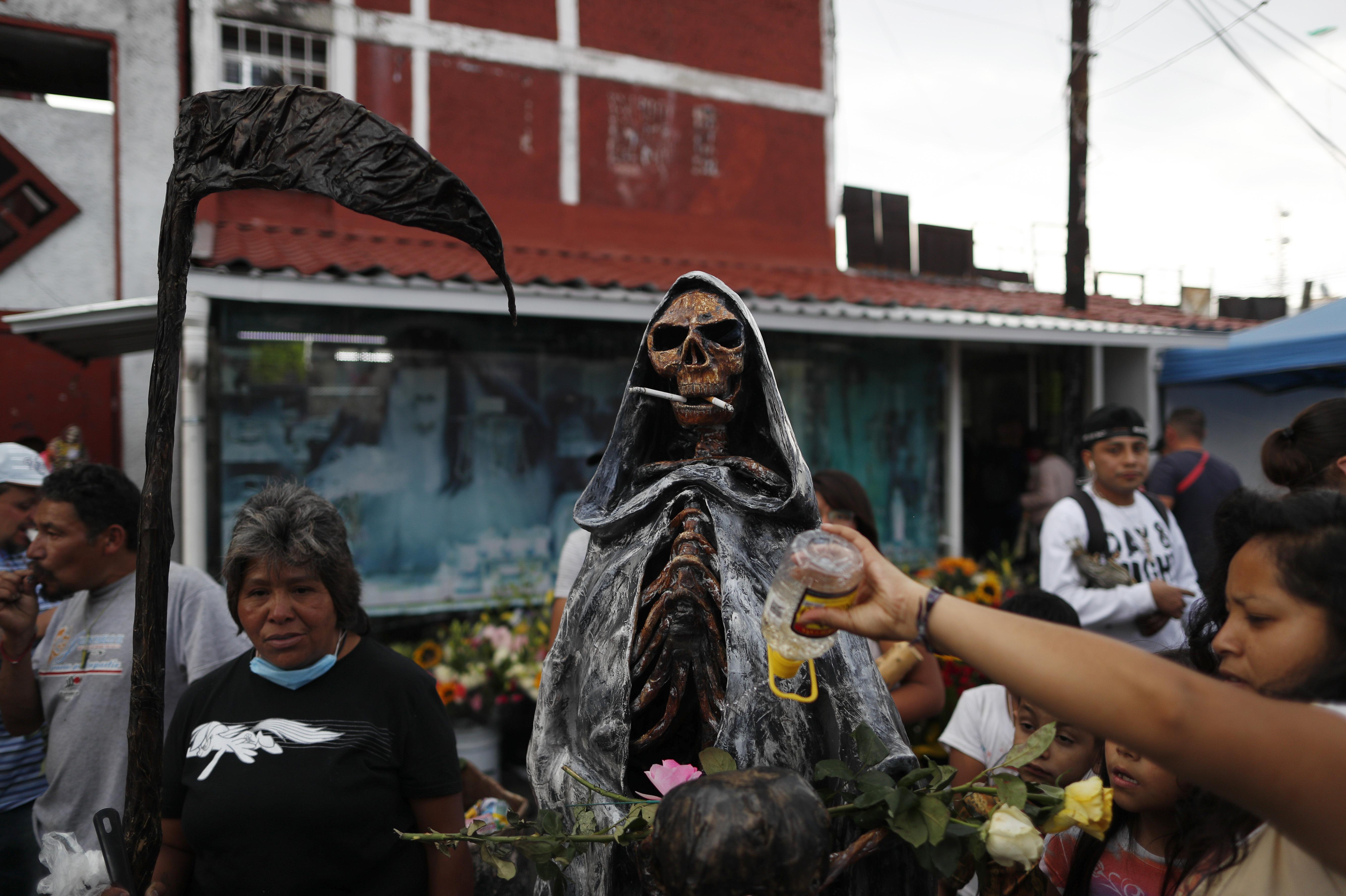 Una mujer arroja alcohol sobre una estatua de la Santa Muerte, o la Santa de la Muerte, cuya boca sostiene dos cigarrillos encendidos que dejaron otros devotos, fuera de su altar en el barrio de Tepito, Ciudad de México, el lunes 1 de junio de 2020. (Foto: AP / Rebecca Blackwell)