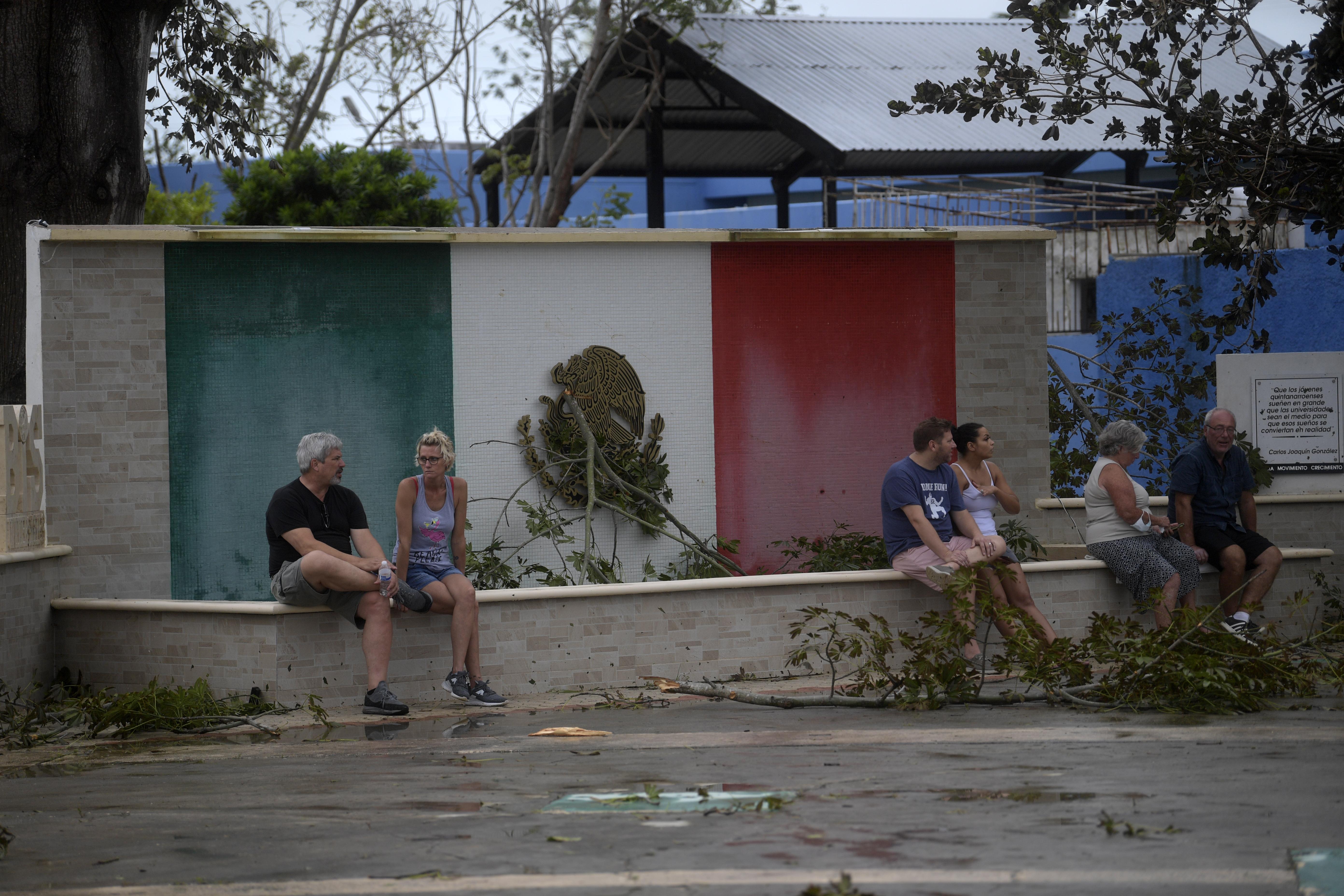 Los turistas permanecen afuera de un refugio después del paso del huracán Delta en Cancún, estado de Quintana Roo, México, el 7 de octubre de 2020.