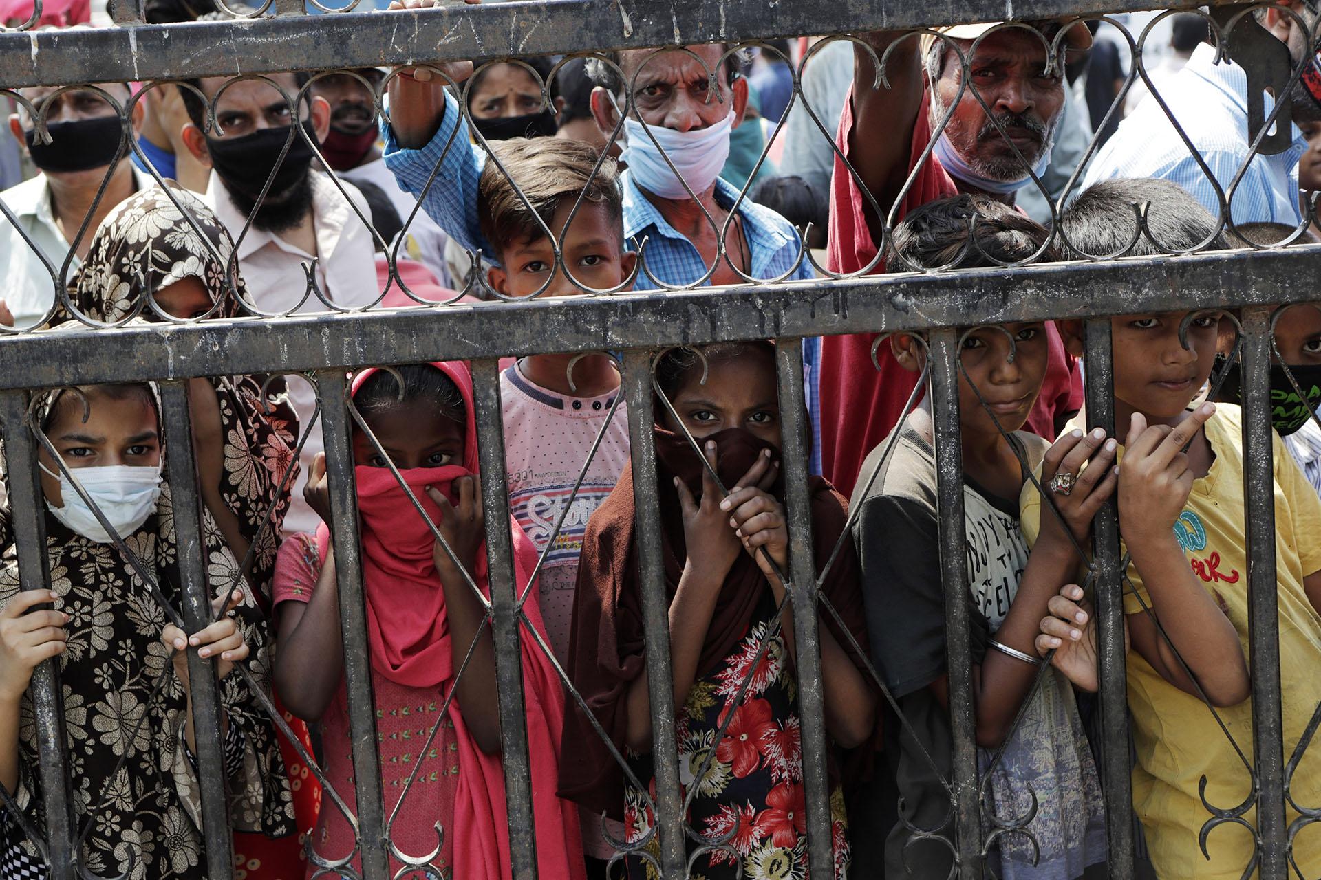 Niños esperan para recibir alimentos gratuitos en un barrio marginal durante la cuarentena por el coronavirus en Mumbai, India, el sábado 18 de abril de 2020. Mientras los gobiernos de todo el mundo tratan de frenar la propagación del coronavirus, la India ha puesto en marcha uno de los experimentos sociales más draconianos de la historia, encerrando a toda su población, incluyendo a unos 176 millones de personas que luchan por sobrevivir con 1,90 dólares al día o menos (AP Photo/Rajanish Kakade)