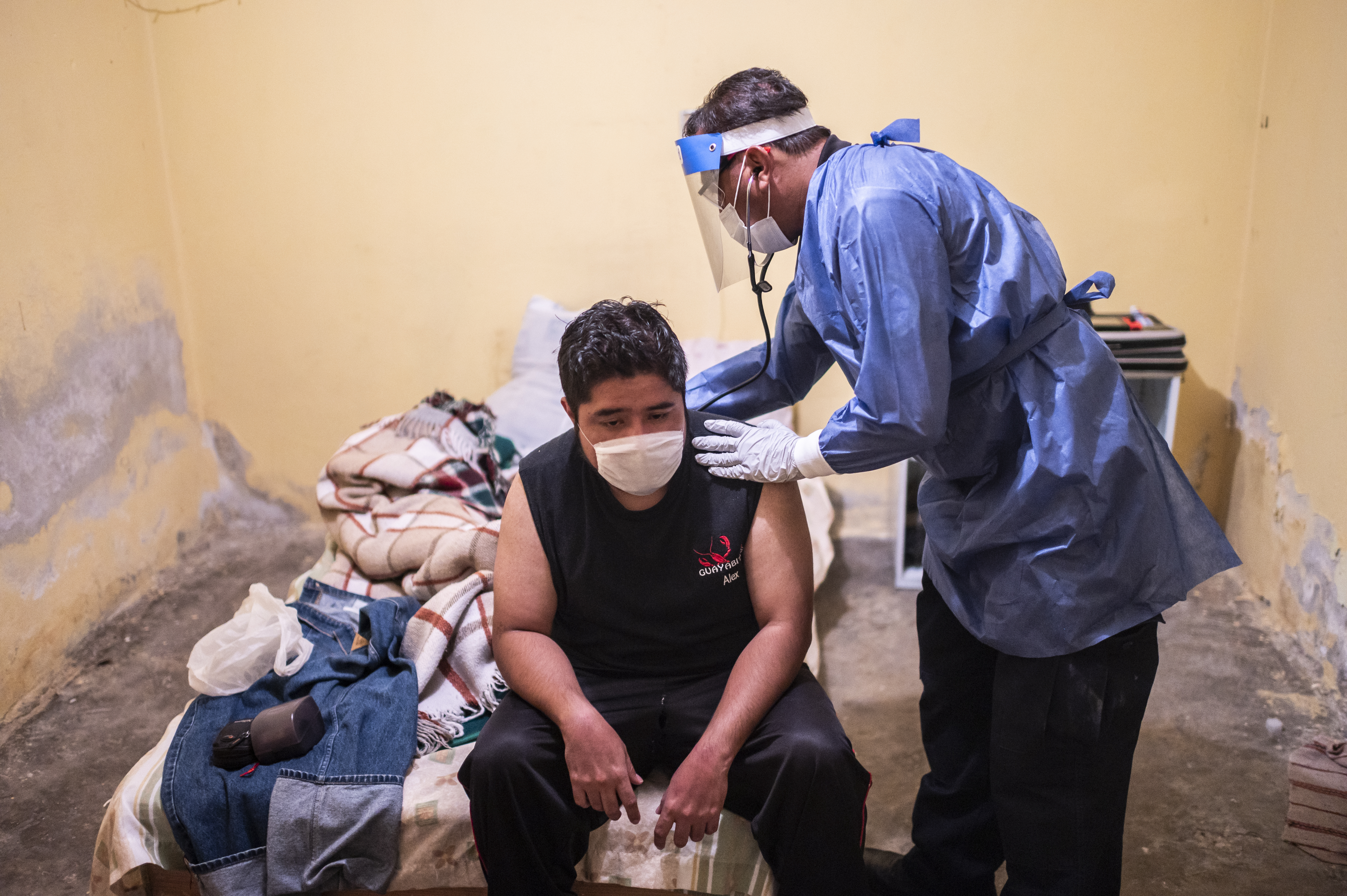 El paramédico Jorge Lino, de 52 años, examina a un hombre con síntomas de COVID-19, en Ciudad Nezahualcóyotl, Estado de México, México, el 22 de junio de 2020 durante la nueva pandemia de coronavirus. (Foto por Pedro PARDO / AFP)