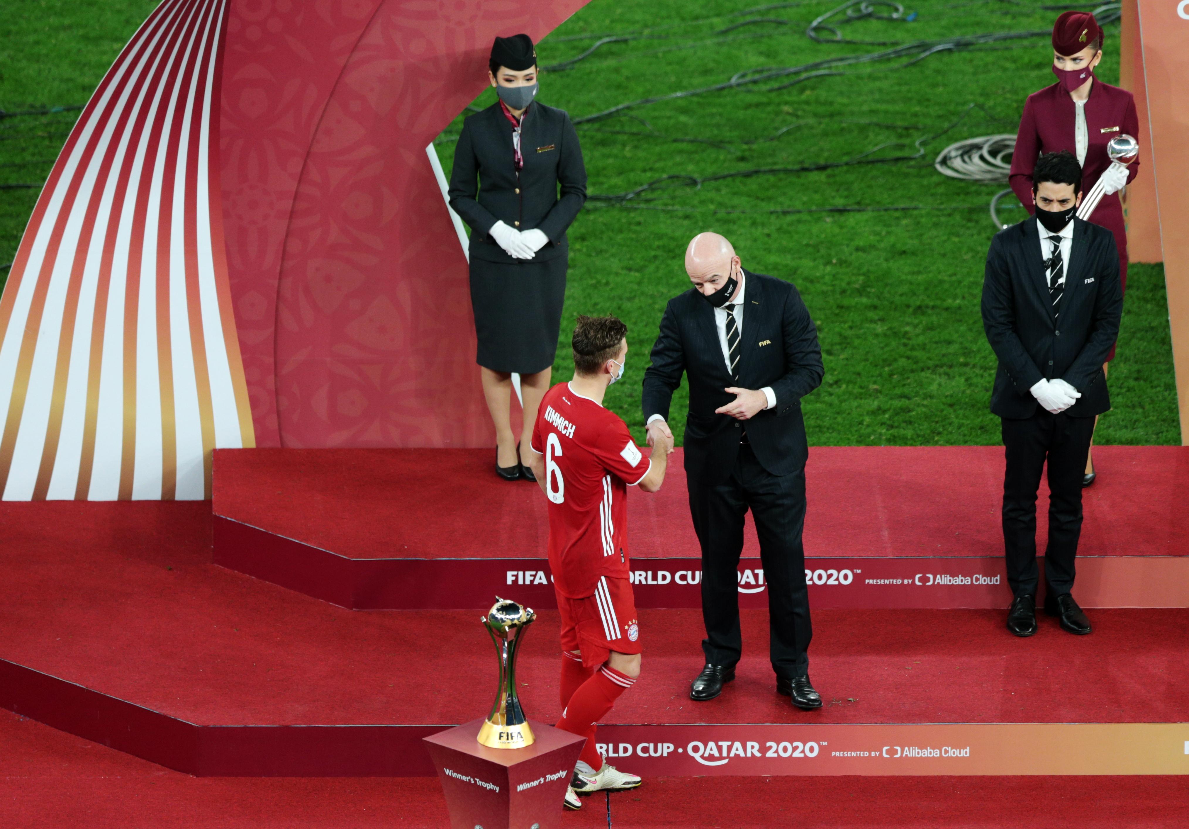 Joshua Kimmich de Bayern Múnich le da la mano al presidente de la FIFA Gianni Infantino.