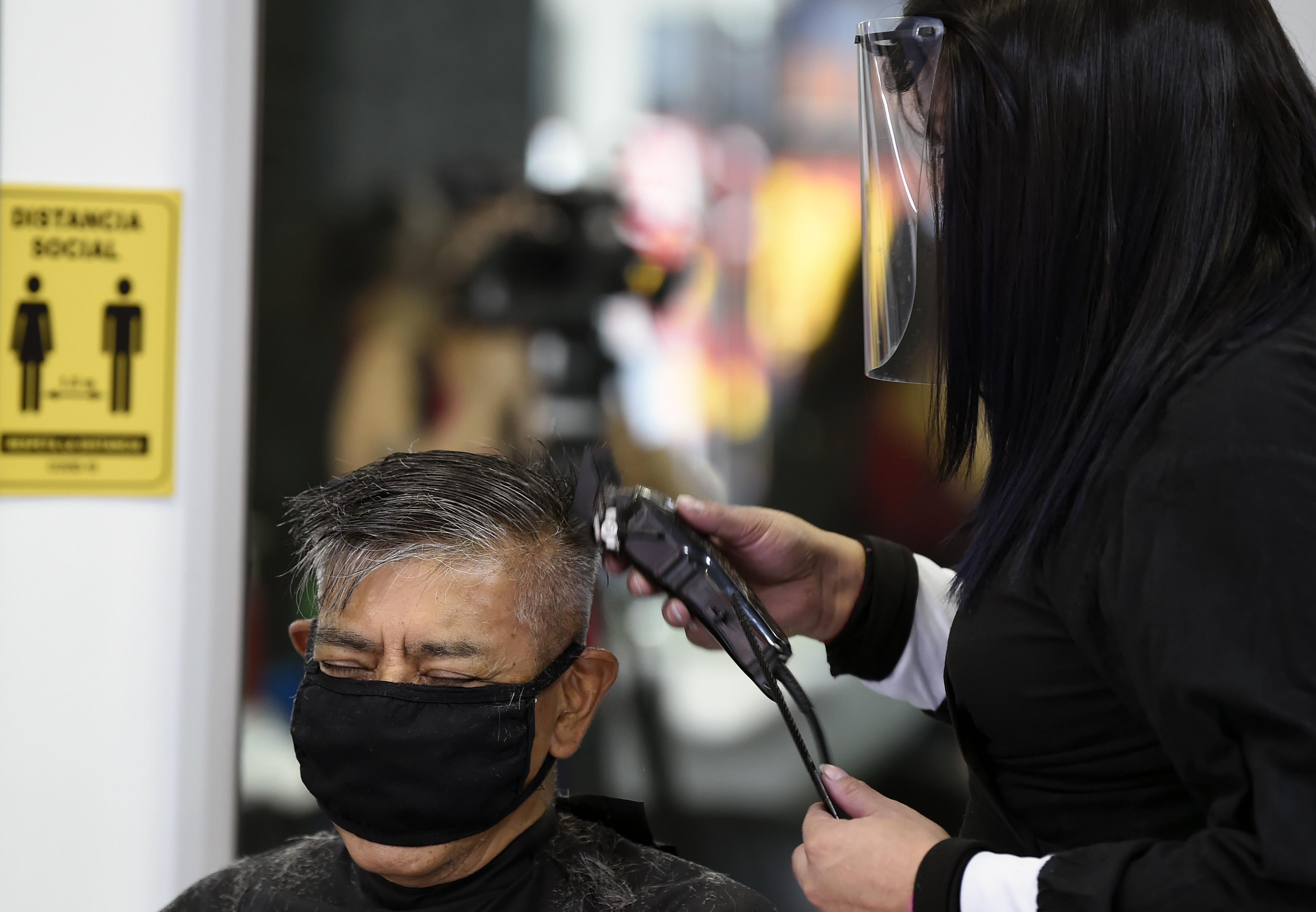 Un cliente se corta el pelo en un salón de belleza, durante la pandemia COVID-19, en la Ciudad de México el 29 de junio de 2020. (Foto: ALFREDO ESTRELLA / AFP)
