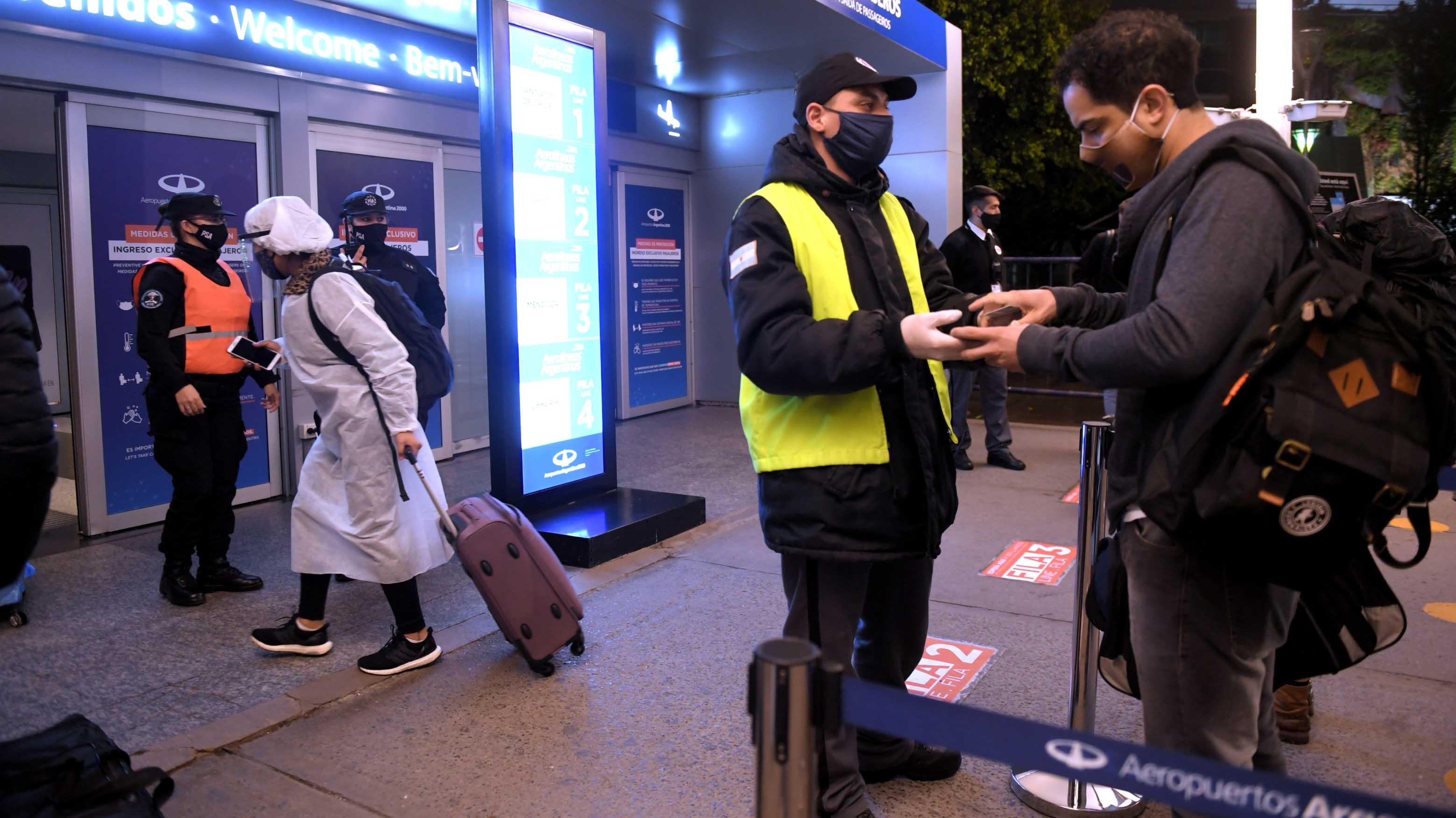 Personal de Ezeiza revisa la documentación de los pasajeros. El aeropuerto Jorge Newbery está siendo remodelado y por ahora no realiza operaciones regulares