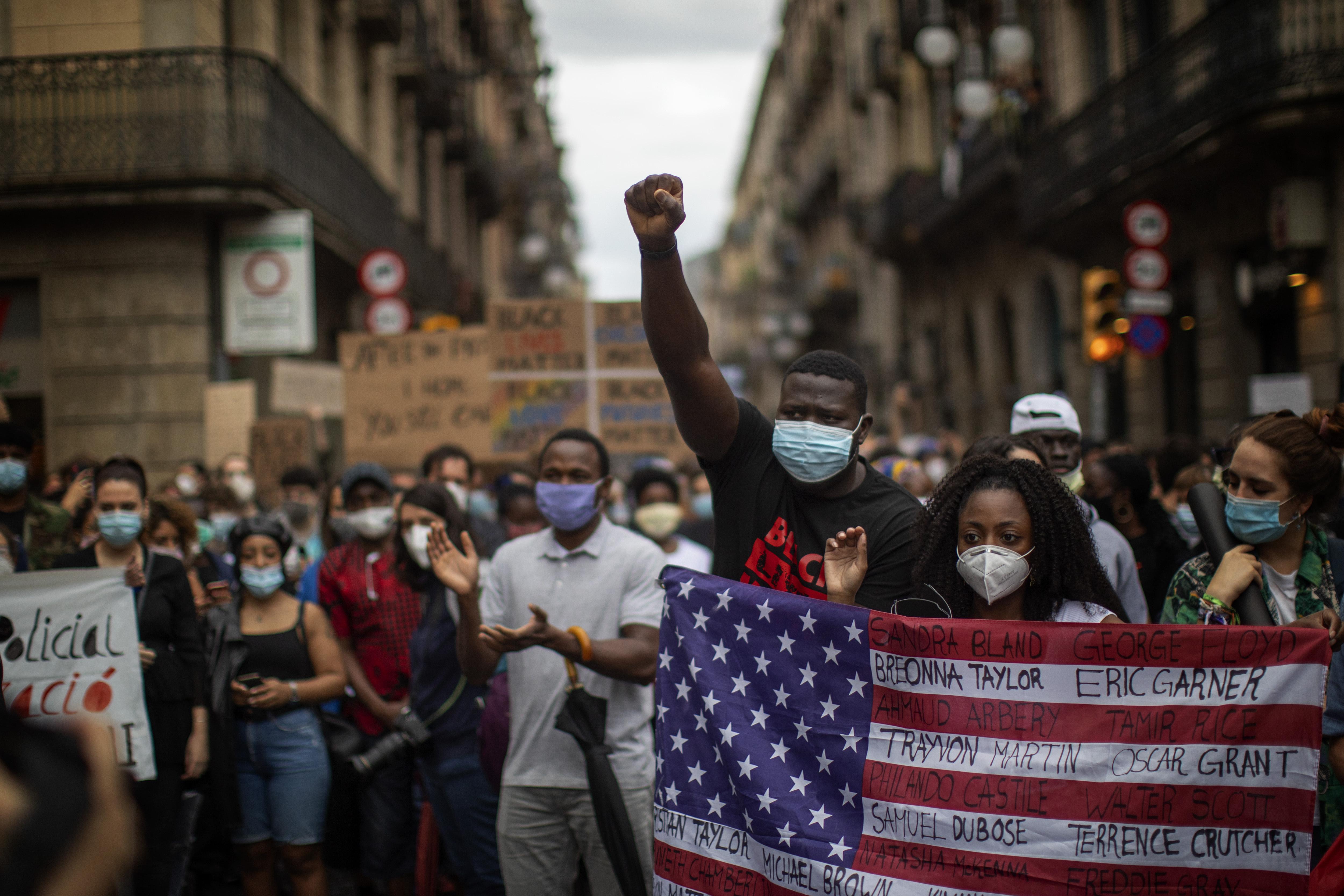 En Barcelona, manifestantes llenaron la plaza de Sant Jaume, donde se encuentra el gobierno regional. Enmascarados y manteniendo su distancia, levantaron carteles en inglés para denunciar el racismo en España y Europa