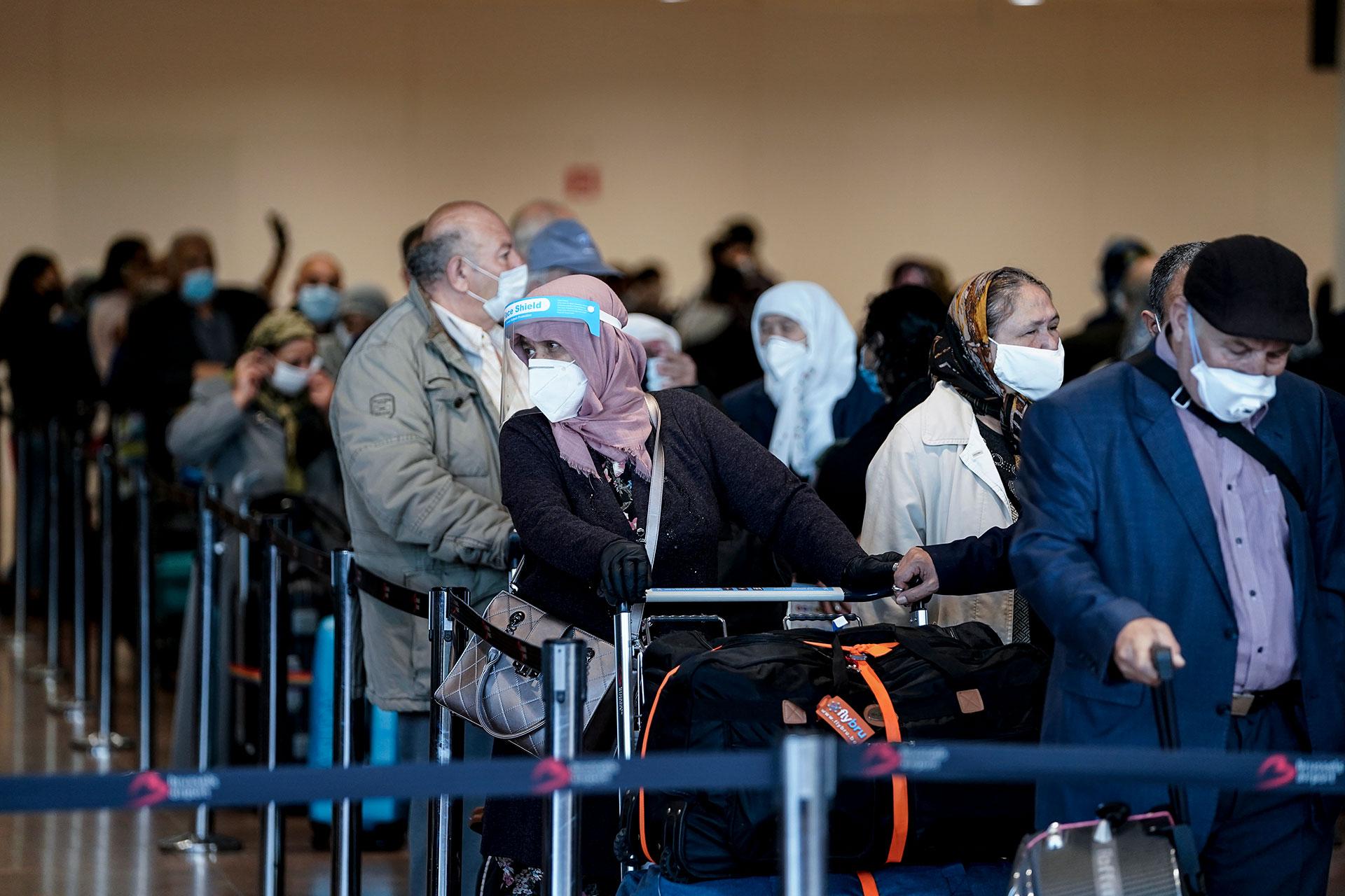 Pasajeros con mascarillas hacen filas para el check-in en el Aeropuerto de Bruselas, en Bélgica.