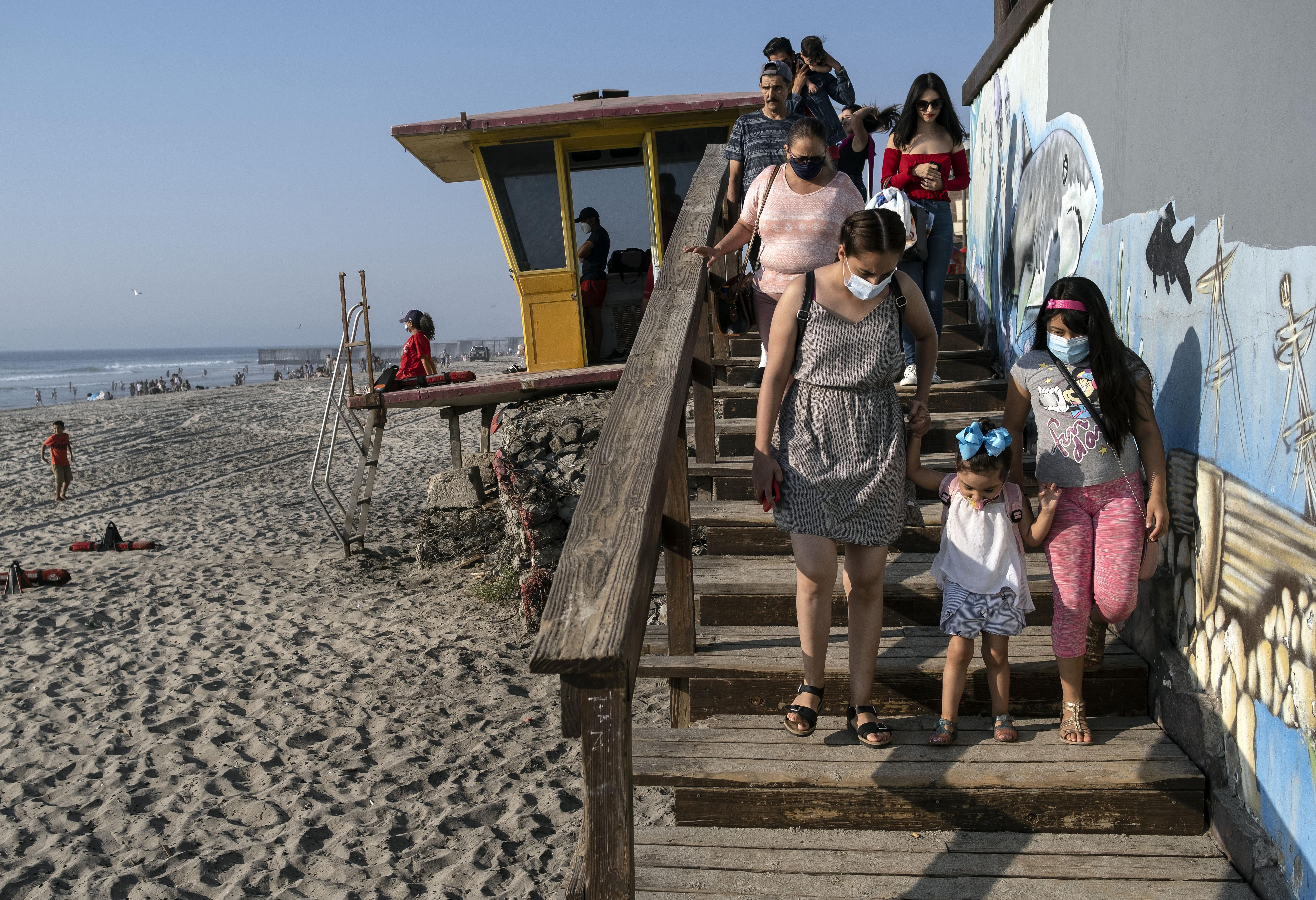 La gente camina hacia la playa en Playas de Tijuana cerca de la frontera entre Estados Unidos y México en Tijuana, estado de Baja California, México, el 3 de octubre de 2020, en medio de la pandemia del coronavirus COVID-19.