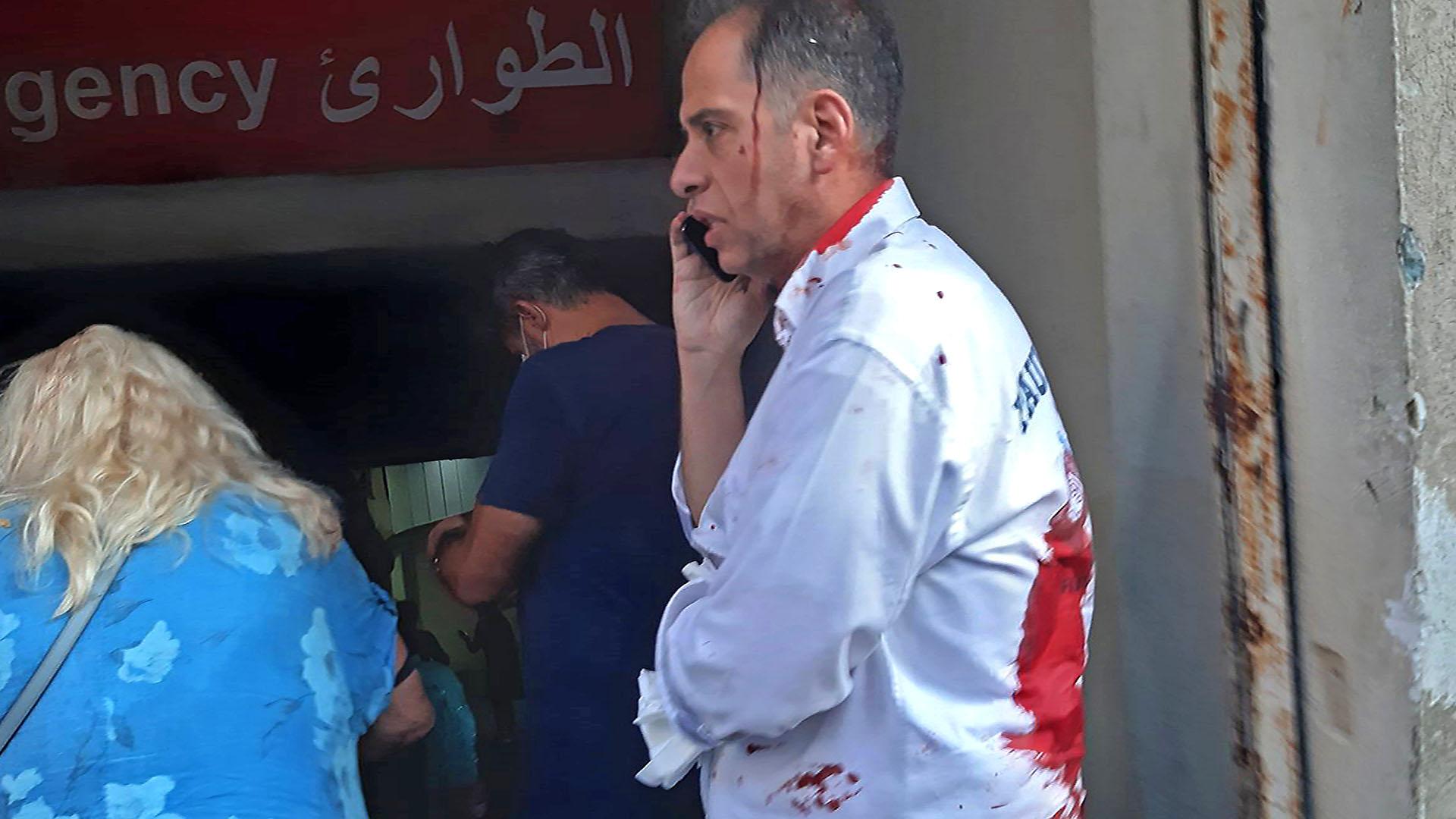 Un hombre con la ropa ensangrentada habla por teléfono en la entrada de una sala de urgencias de un hospital en el distrito de Hamra de Beirut (Foto de Janine Haidar/ AFP)