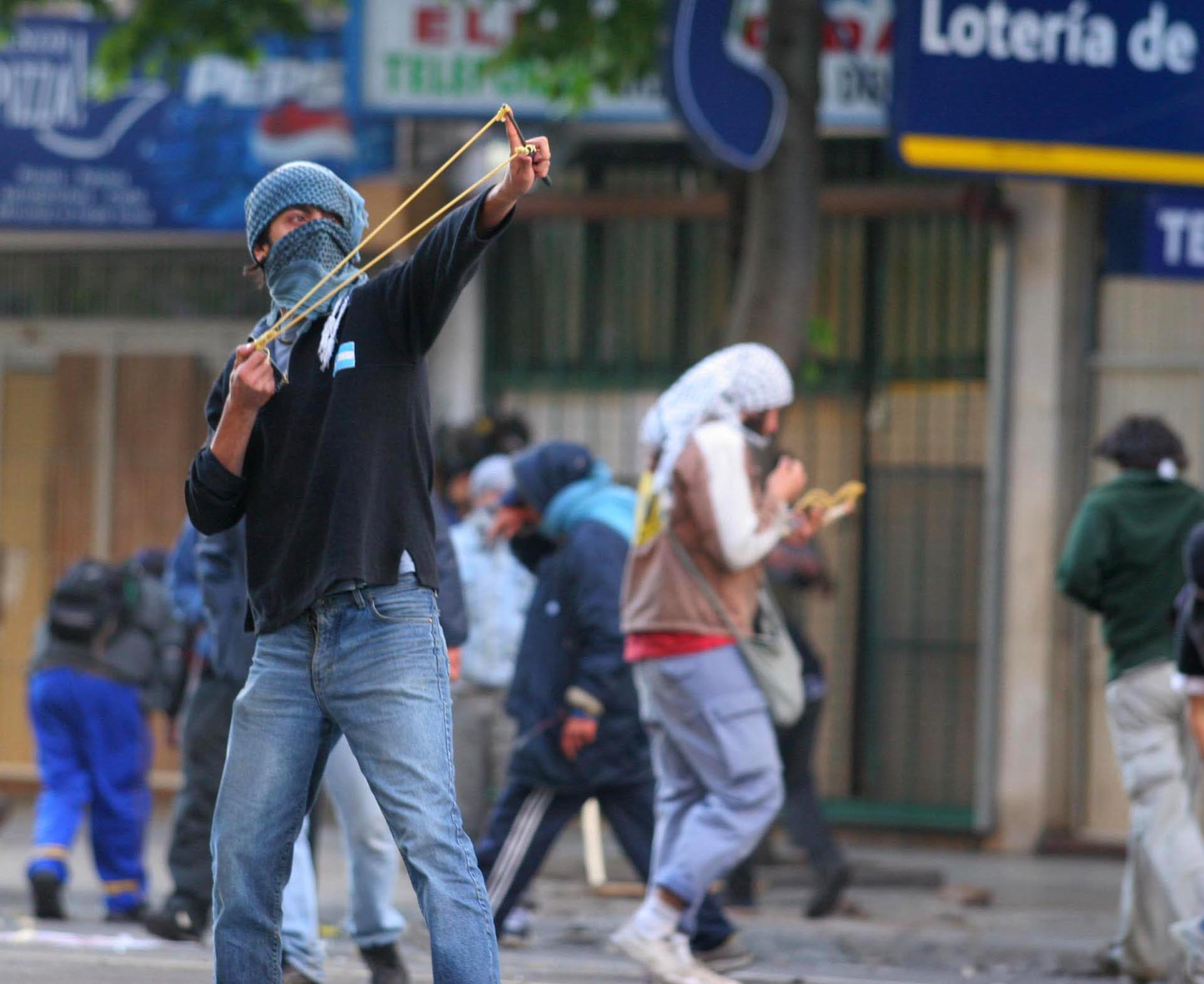 Un manifestante arroja piedras con una gomera durante la marcha en rechazo a la visita del Presidente de EEUU