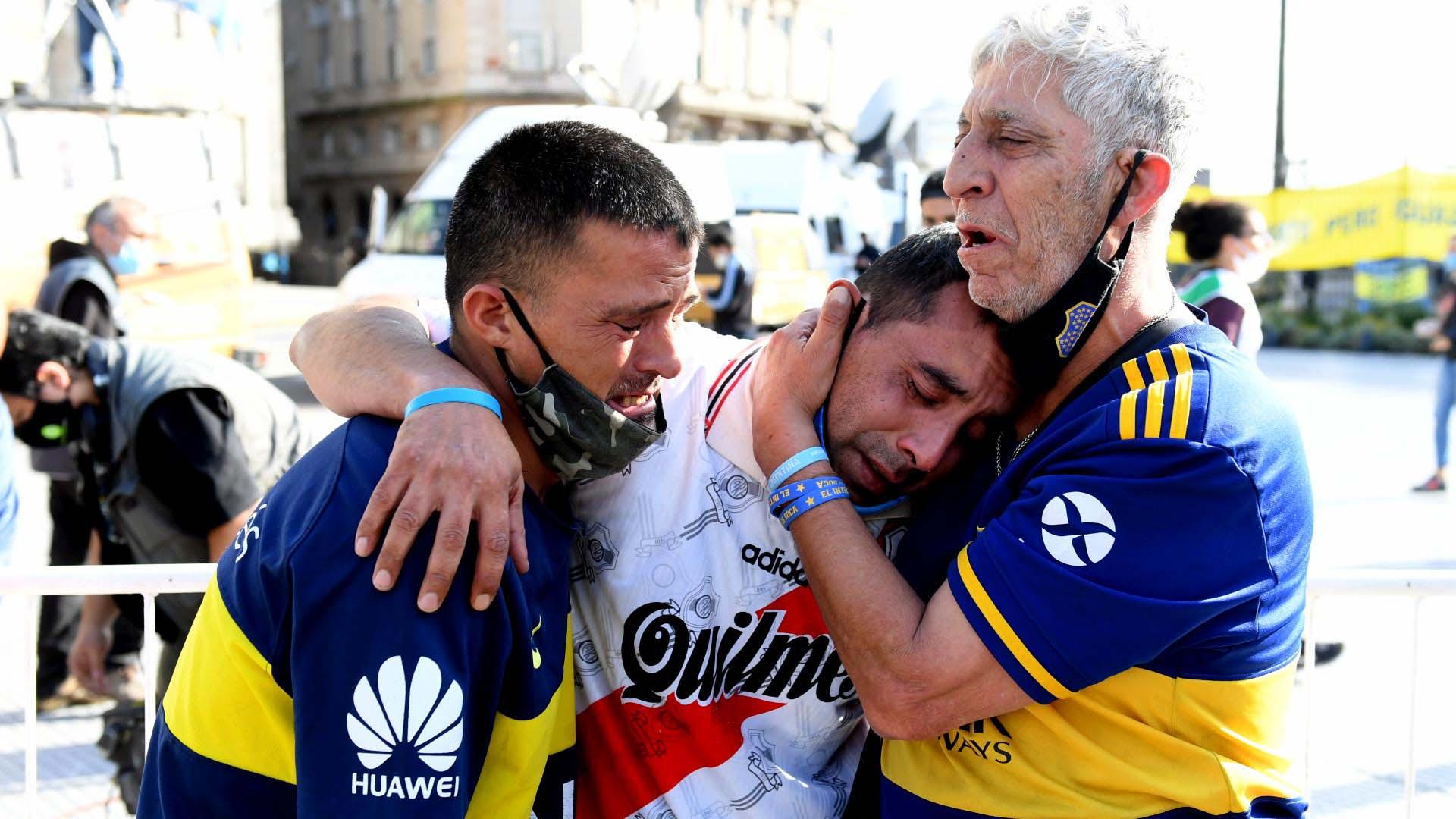 La foto que recurrió el mundo: un hincha de River abraza y es abrazado por dos hinchas de Boca a la salida del velatorio de Diego Armando Maradona organizado en la Casa Rosada el 26 de noviembre