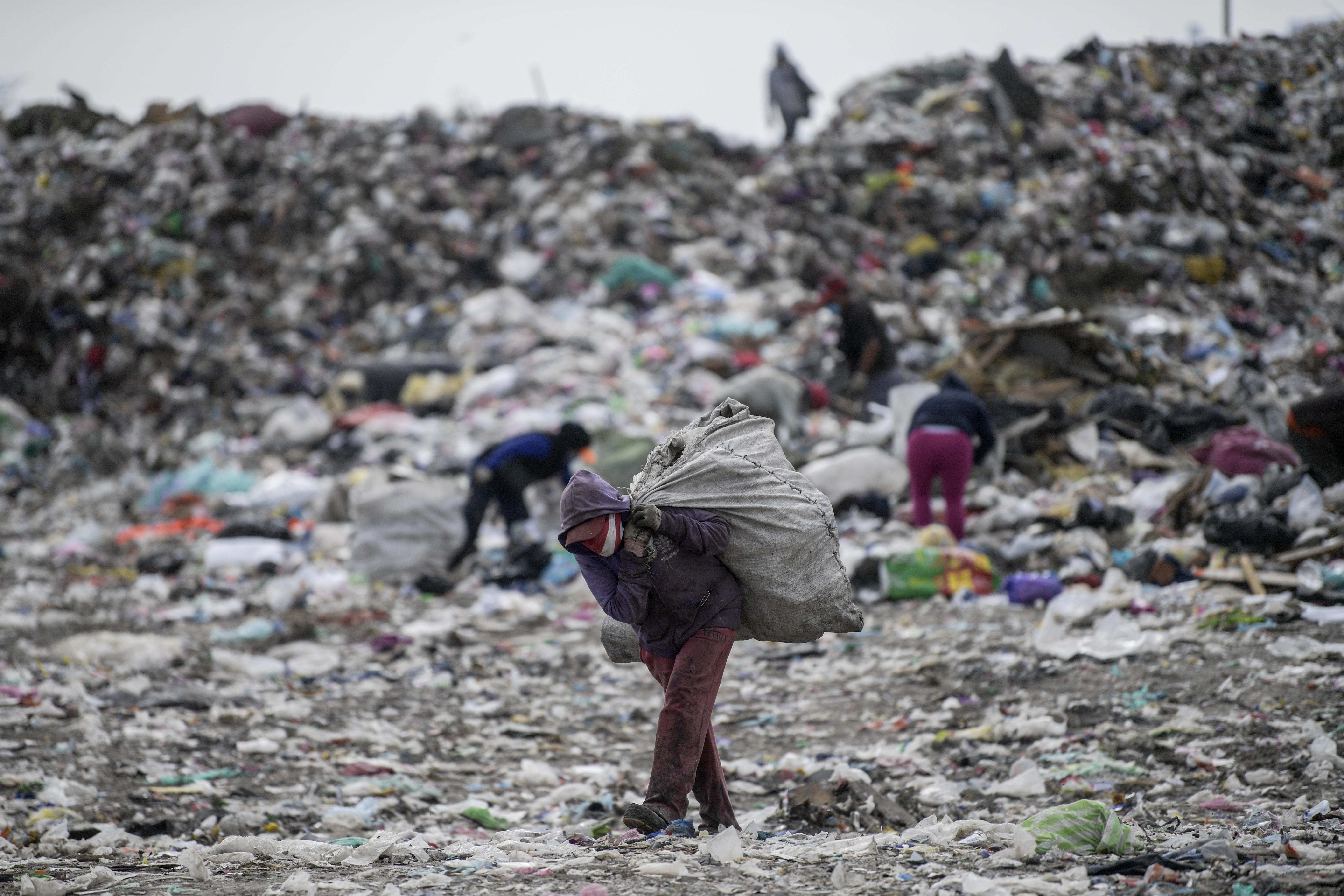 Un recolector lleva una bolsa en el basurero