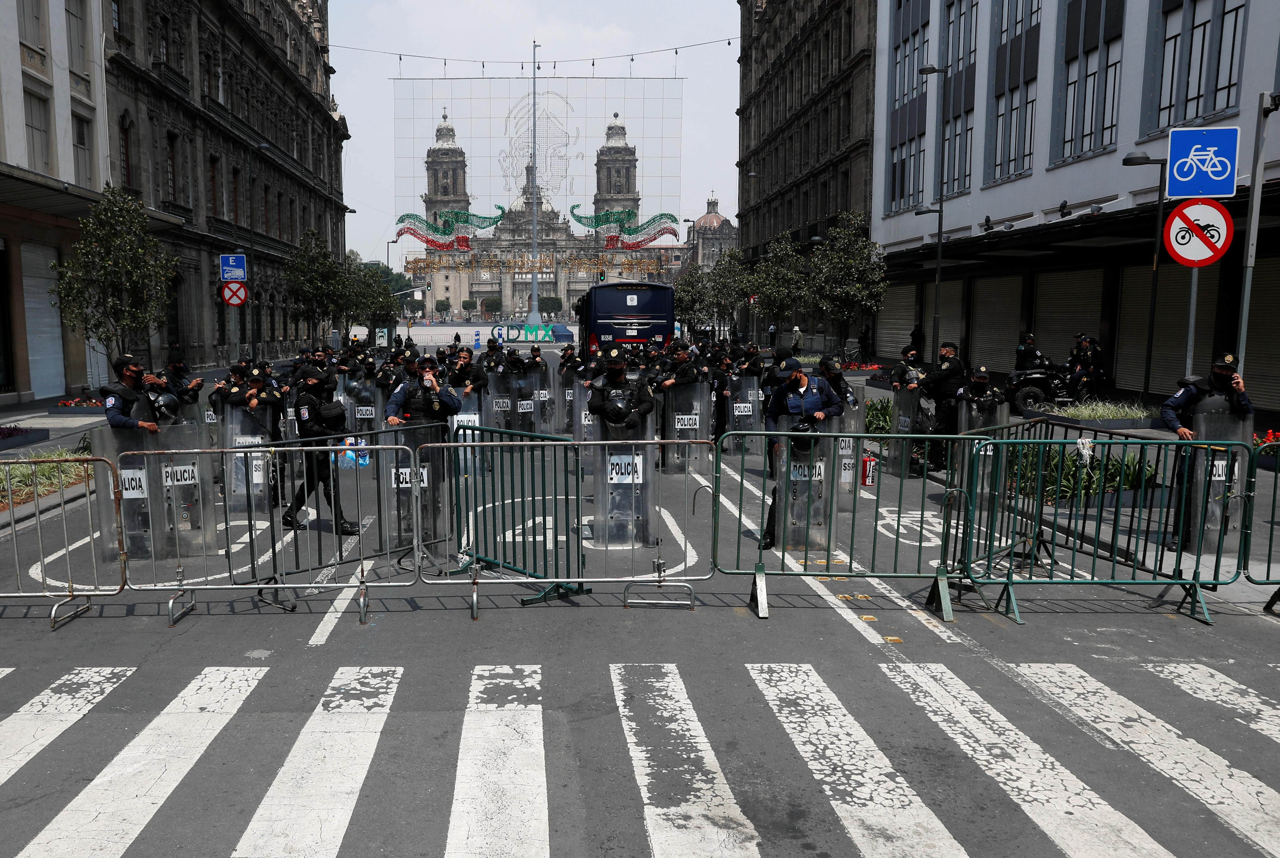 Agentes de policía montan guardia mientras familiares de estudiantes desaparecidos asisten a una protesta frente a la Corte Suprema de Justicia, antes del sexto aniversario de la desaparición de 43 estudiantes de la Escuela de Formación de Maestros de Ayotzinapa, en la Ciudad de México, México 23 de septiembre de 2020.