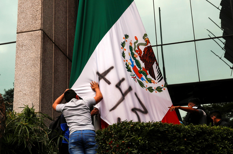 Alumnos de la Escuela de Magisterio de Ayotzinapa junto a la bandera mexicana que tiene pintado