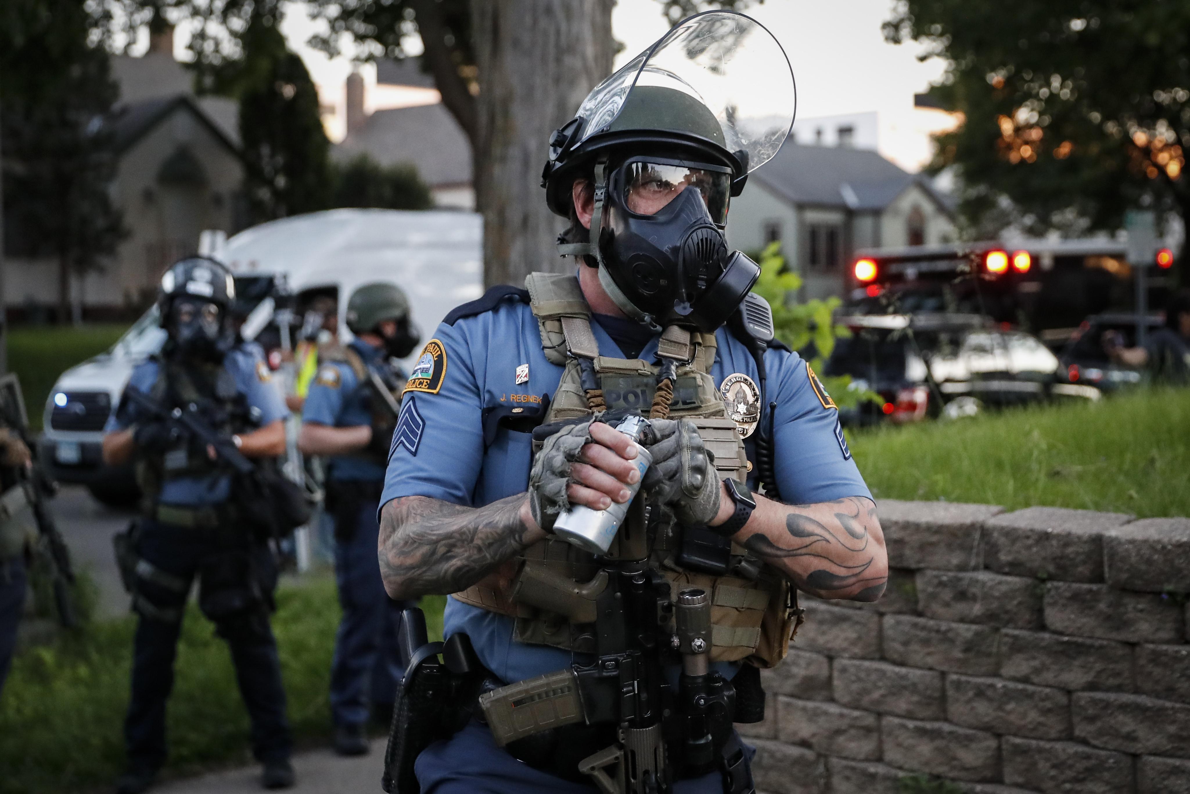 Un oficial de policía se prepara para lanzar un bote de gas lacrimógeno a los manifestantes en St. Paul (AP Photo/John Minchillo)