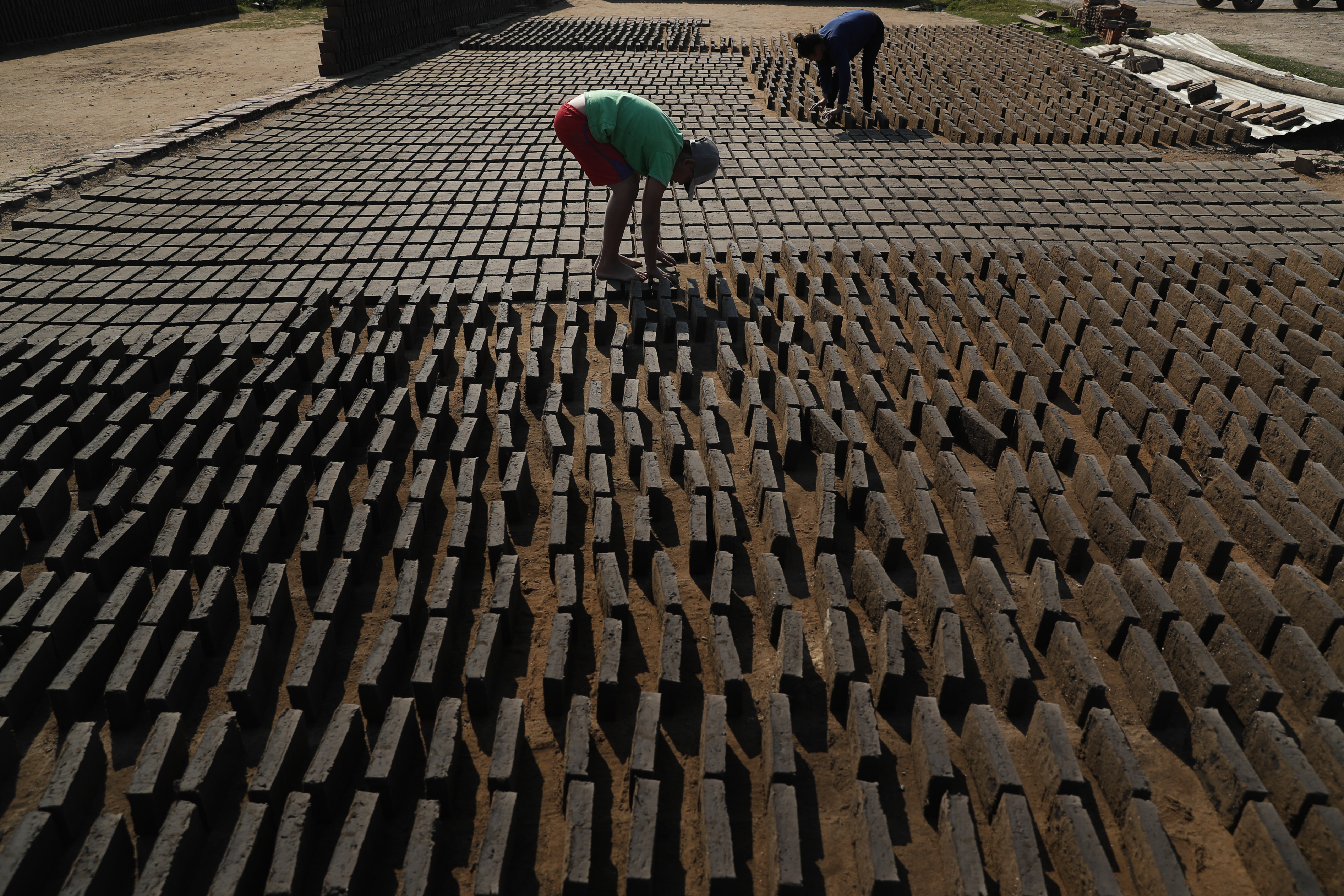 Cristian, en el centro, voltea ladrillos de arcilla de lado mientras se secan al sol antes de colocarlos en un horno en una pequeña fábrica de ladrillos en Tobati, Paraguay, el lunes 24 de agosto de 2020.