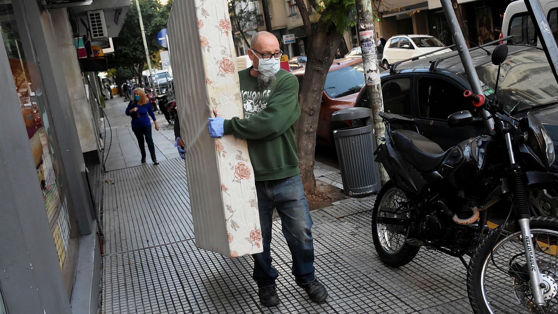 Un empleado de una empresa mudanzas traslada un colchón en medio de la calle