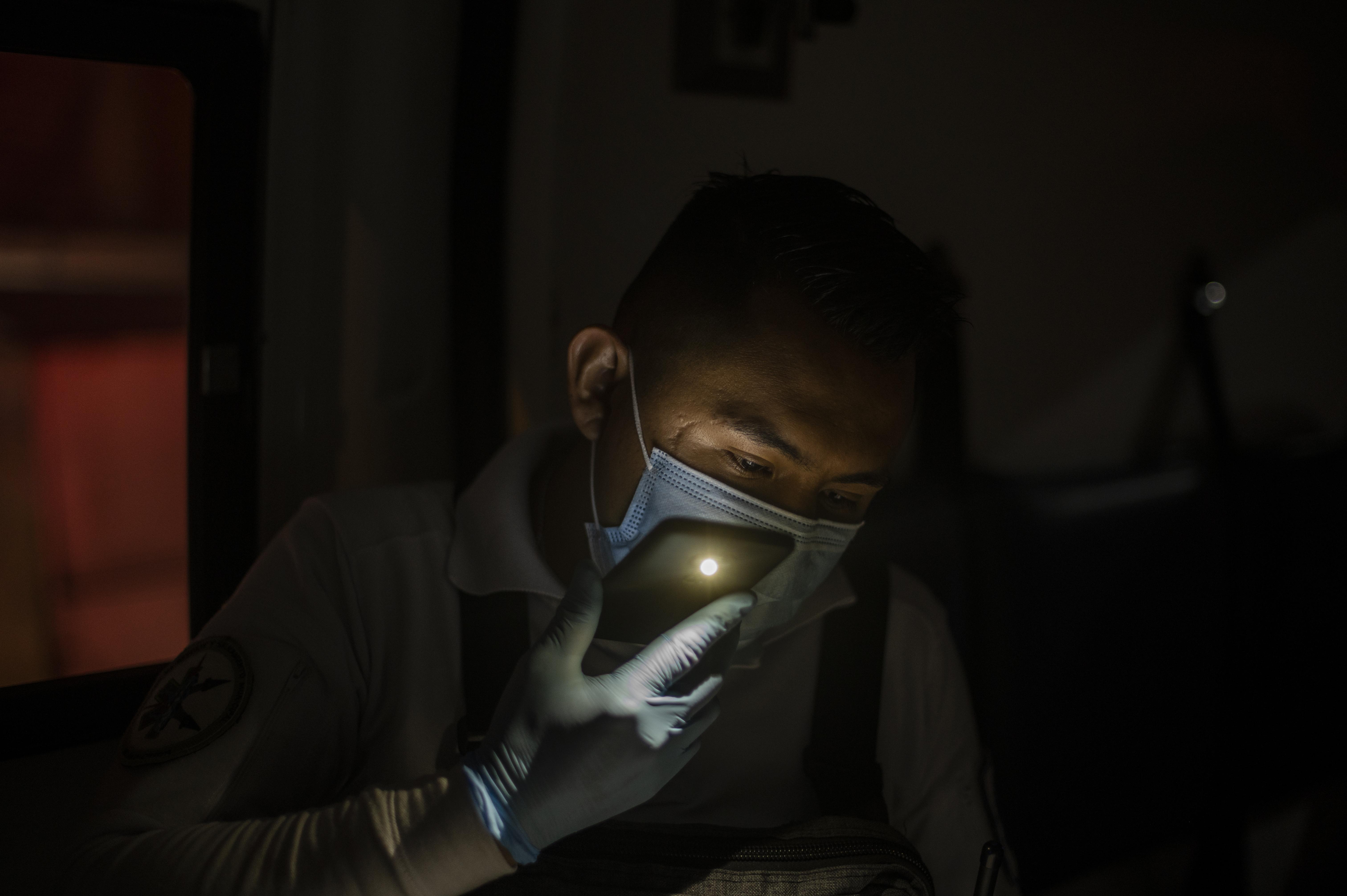El paramédico Jesús Sholndick, de 29 años, recibe una llamada de ayuda de una anciana con problemas de presión arterial en Ciudad Nezahualcóyotl, Estado de México, México, el 18 de junio de 2020 durante la nueva pandemia de coronavirus COVID-19. (Foto por Pedro PARDO / AFP)
