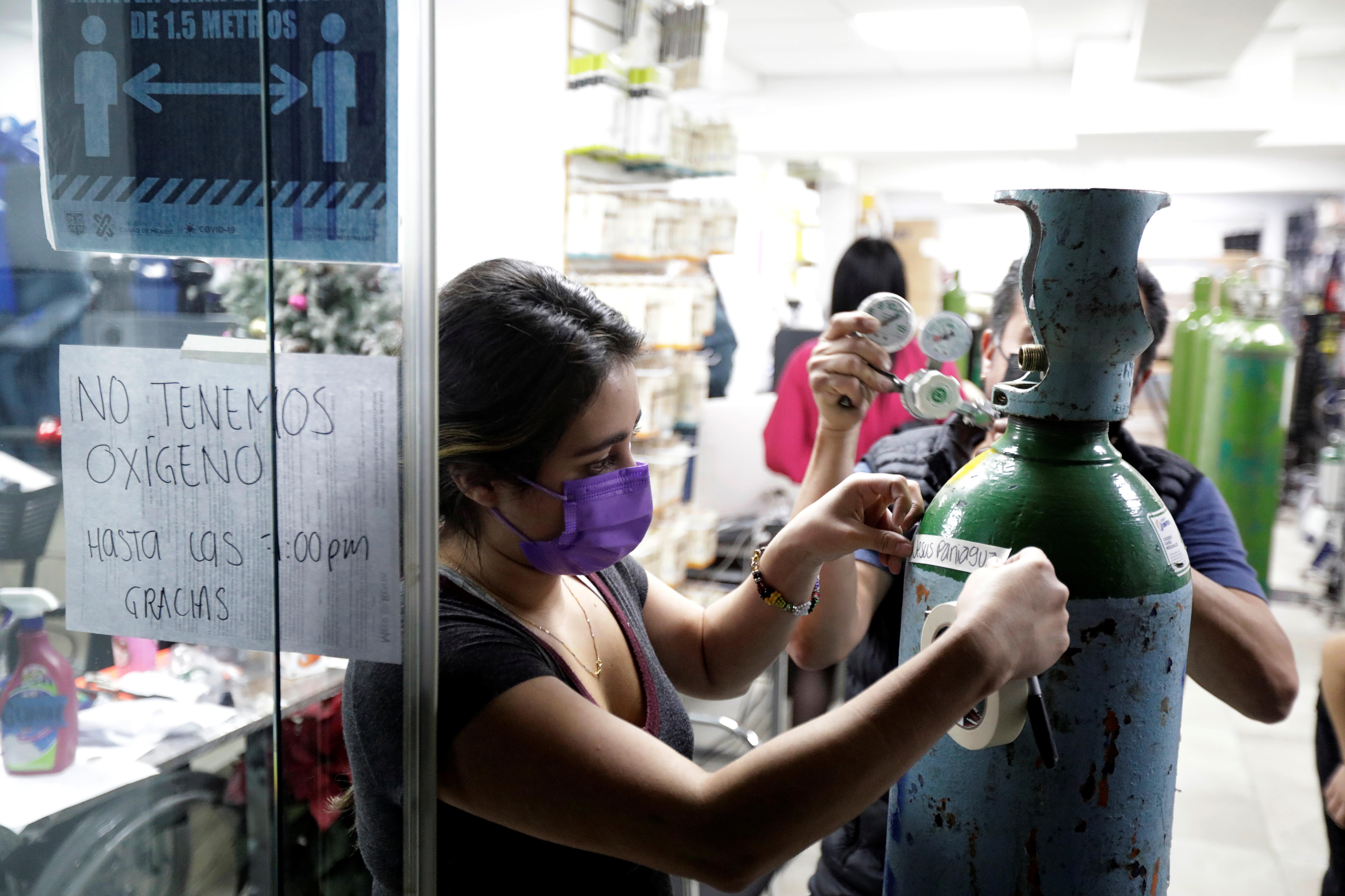 Un empleado coloca un trozo de cinta con el nombre de un paciente conCOVID-19 en un tanque de oxígeno, para llenarlo en una tienda de suministros médicos, en la Ciudad de México, México, el 15 de diciembre de 2020. Fotografía tomada el 15 de diciembre.