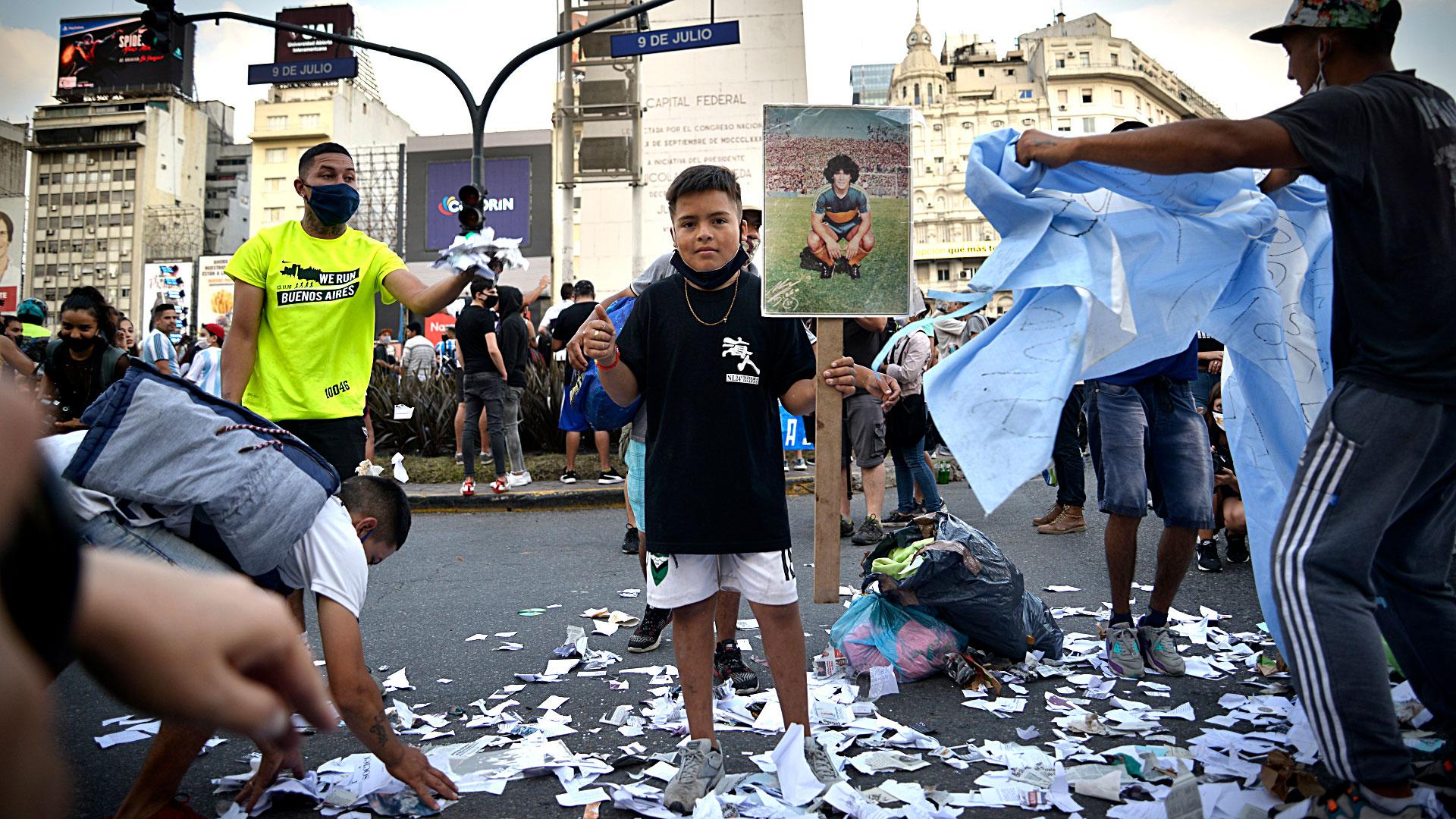 Los papelitos que lo bañaron en las salidas al campo de juego reposan en el suelo. Y un niño lamenta su partida junto a su imagen (Gustavo Gavotti)