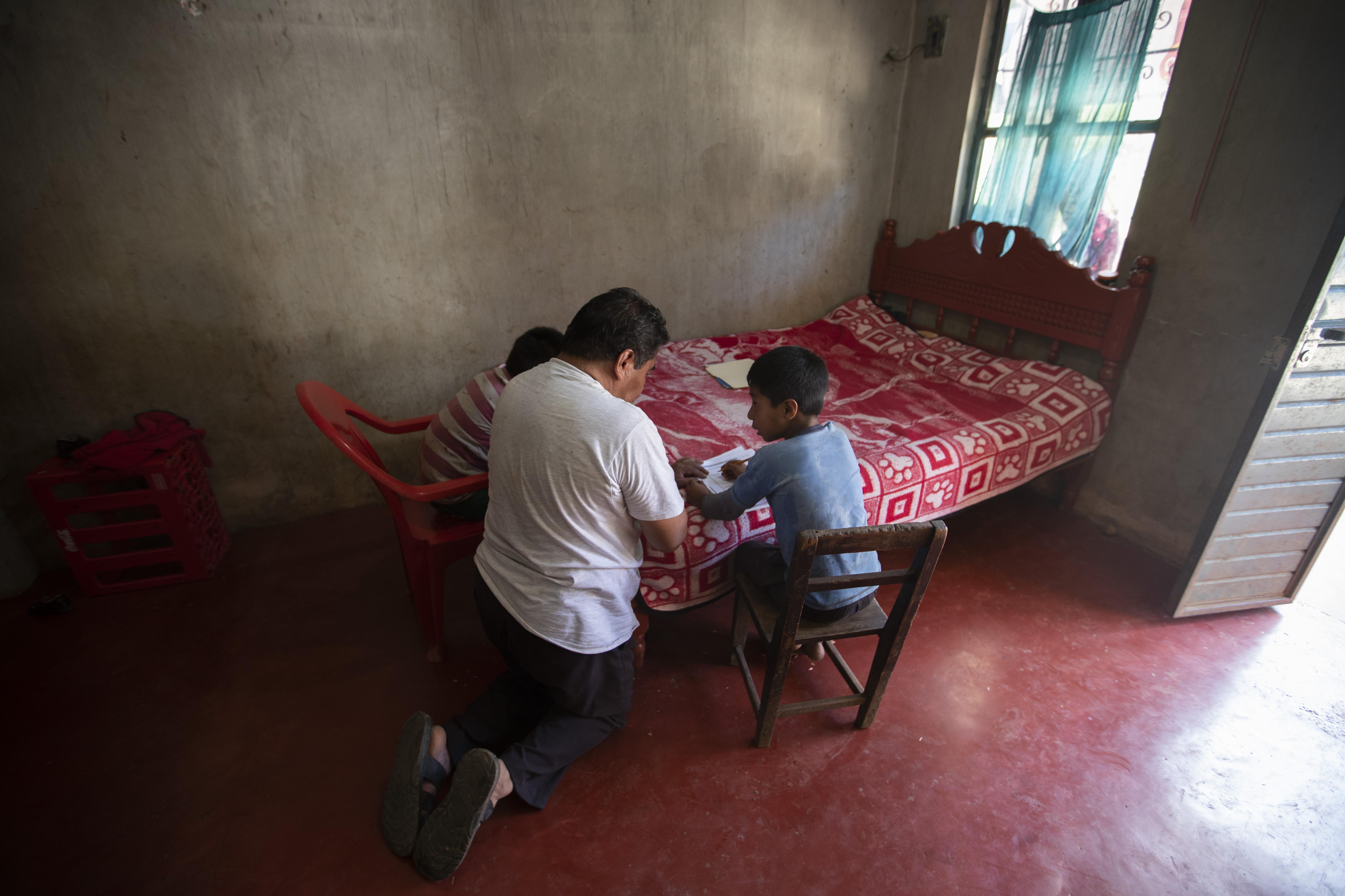 """Usando una cama como escritorio, Agustín Vázquez ayuda a sus hijos Samuel y Héctor con sus tareas escolares entregadas por maestros en medio de la nueva pandemia de coronavirus en su casa en Nuevo Yibeljoj, estado de Chiapas, México, el viernes 11 de septiembre de 2020. """"Lo intento , pero no es lo mismo que un maestro, porque yo soy agricultor """", dijo Agustín."""
