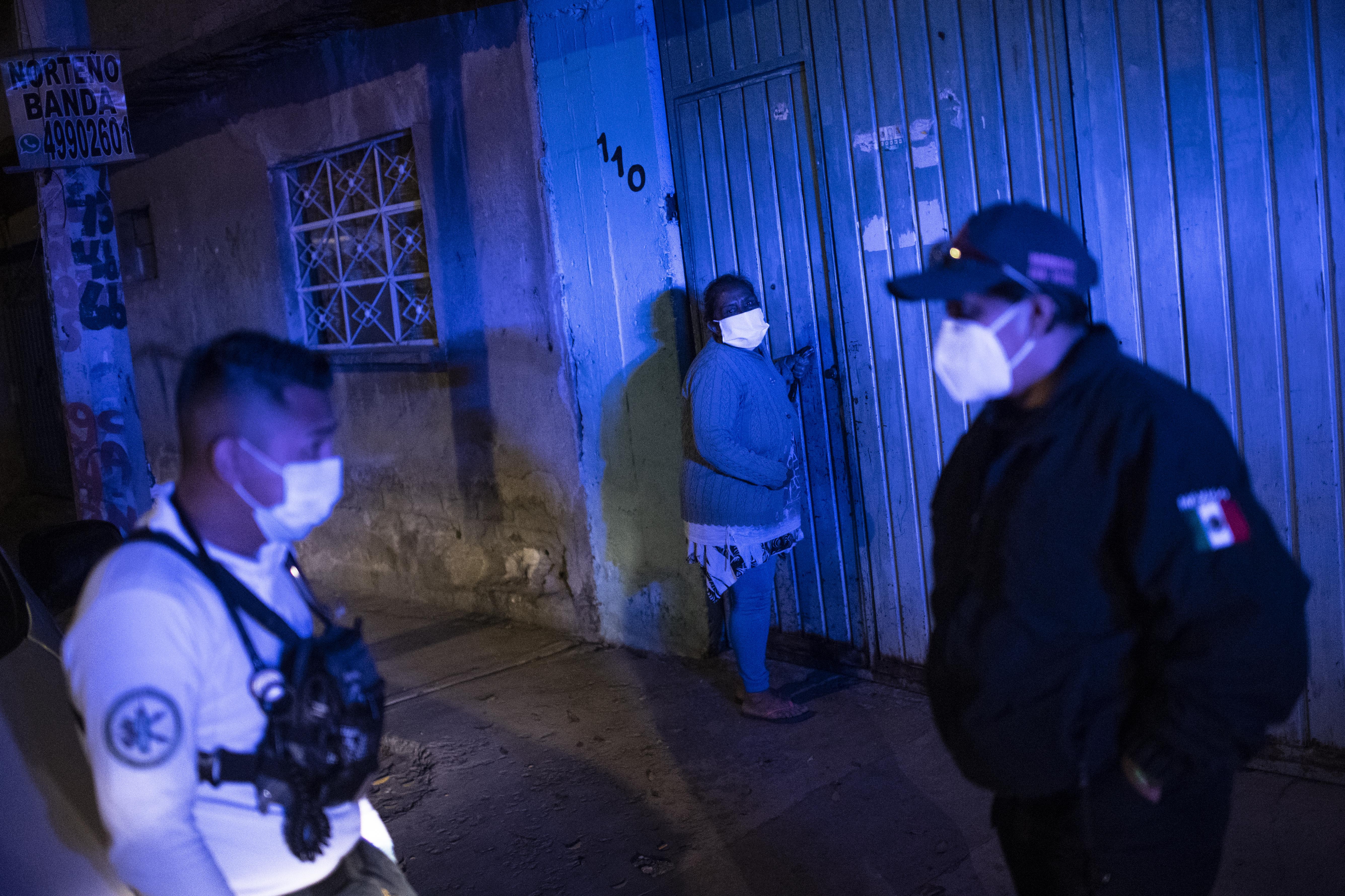 El paramédico Jesús Sholndick, de 29 años, (I) llega para controlar a una anciana con problemas de presión arterial en Ciudad Nezahualcóyotl, Estado de México, México, el 18 de junio de 2020 durante la nueva pandemia de coronavirus de COVID-19. (Foto por Pedro PARDO / AFP)