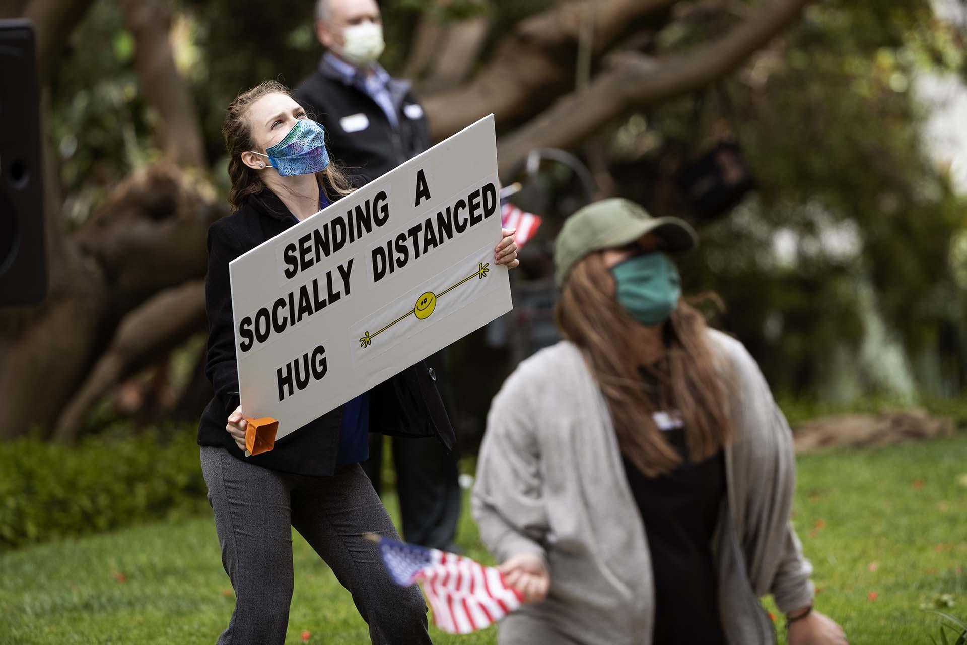Empleados de Vi en el complejo del retiro La Jolla sostienen carteles y banderas para los residentes en San Diego (AP Photo/Gregory Bull)