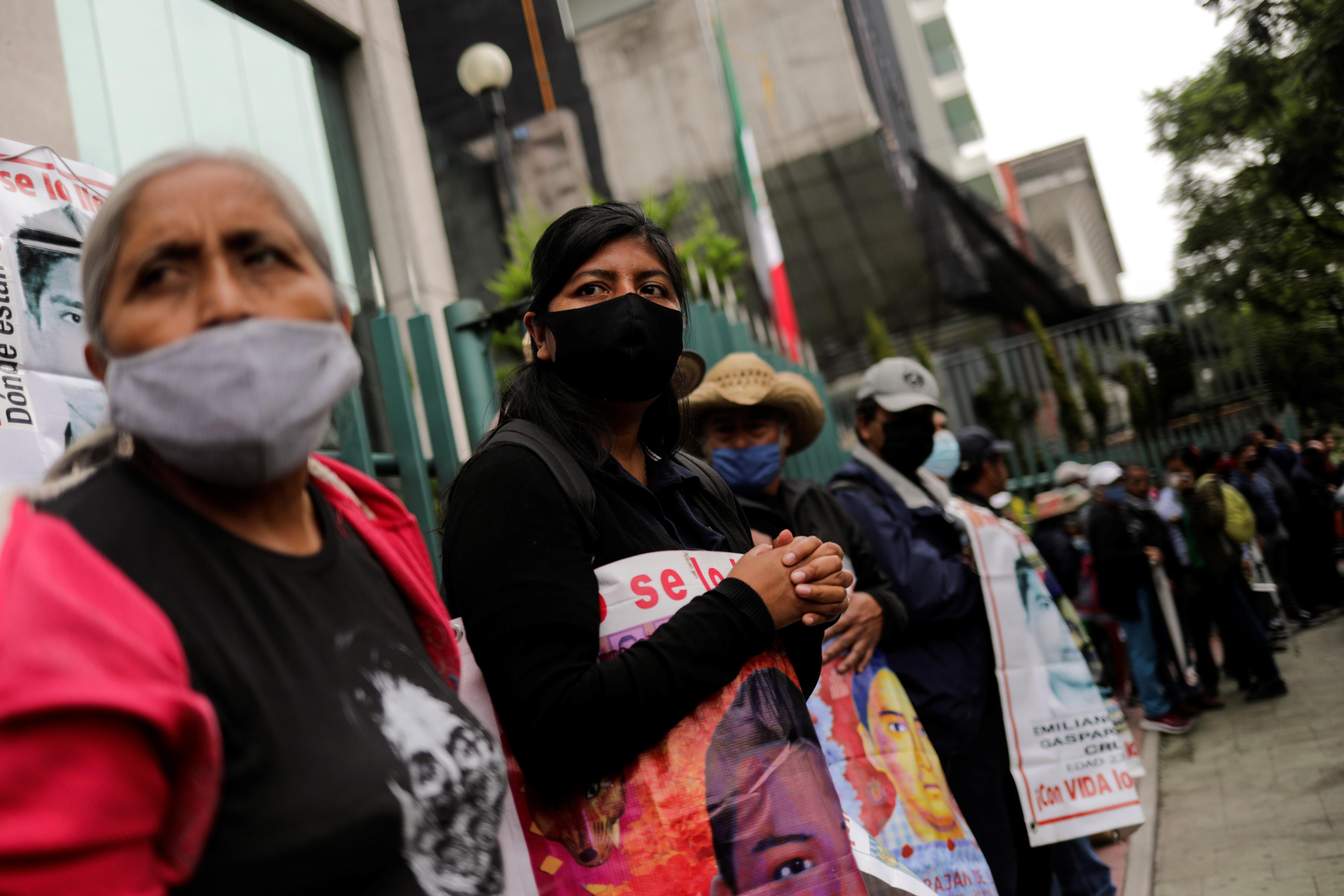 Familiares de estudiantes desaparecidos sostienen carteles durante una protesta frente a la Corte Suprema de Justicia, antes del sexto aniversario de la desaparición de 43 estudiantes de la Escuela de Formación de Maestros de Ayotzinapa, en la Ciudad de México, México 23 de septiembre de 2020.