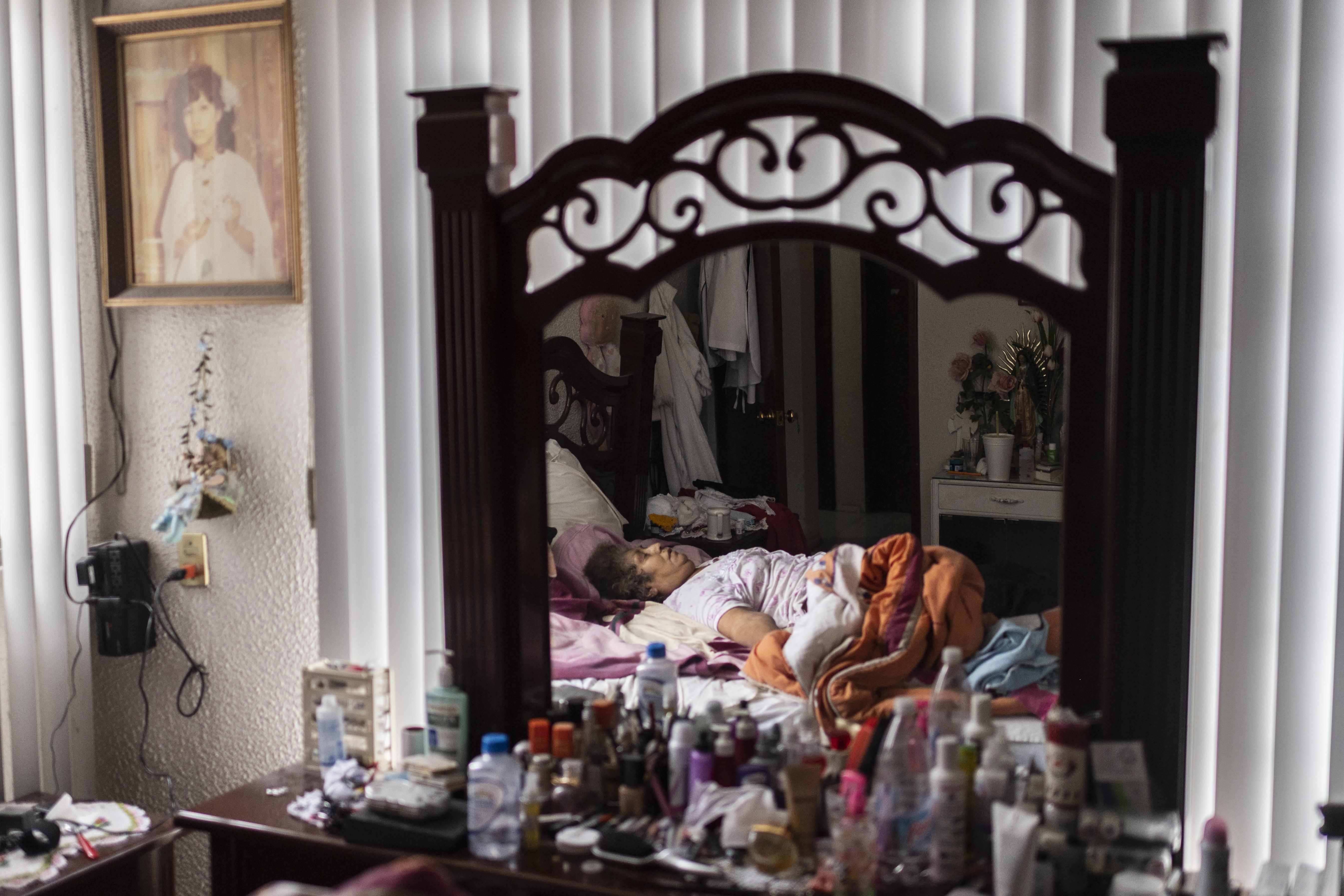Una mujer que murió por complicaciones de enfermedades crónicas y mostró síntomas de COVID-19, yace en su cama en Ciudad Nezahualcóyotl, Estado de México, México, el 21 de junio de 2020 durante la nueva pandemia de coronavirus de COVID-19. (Foto por Pedro PARDO / AFP)