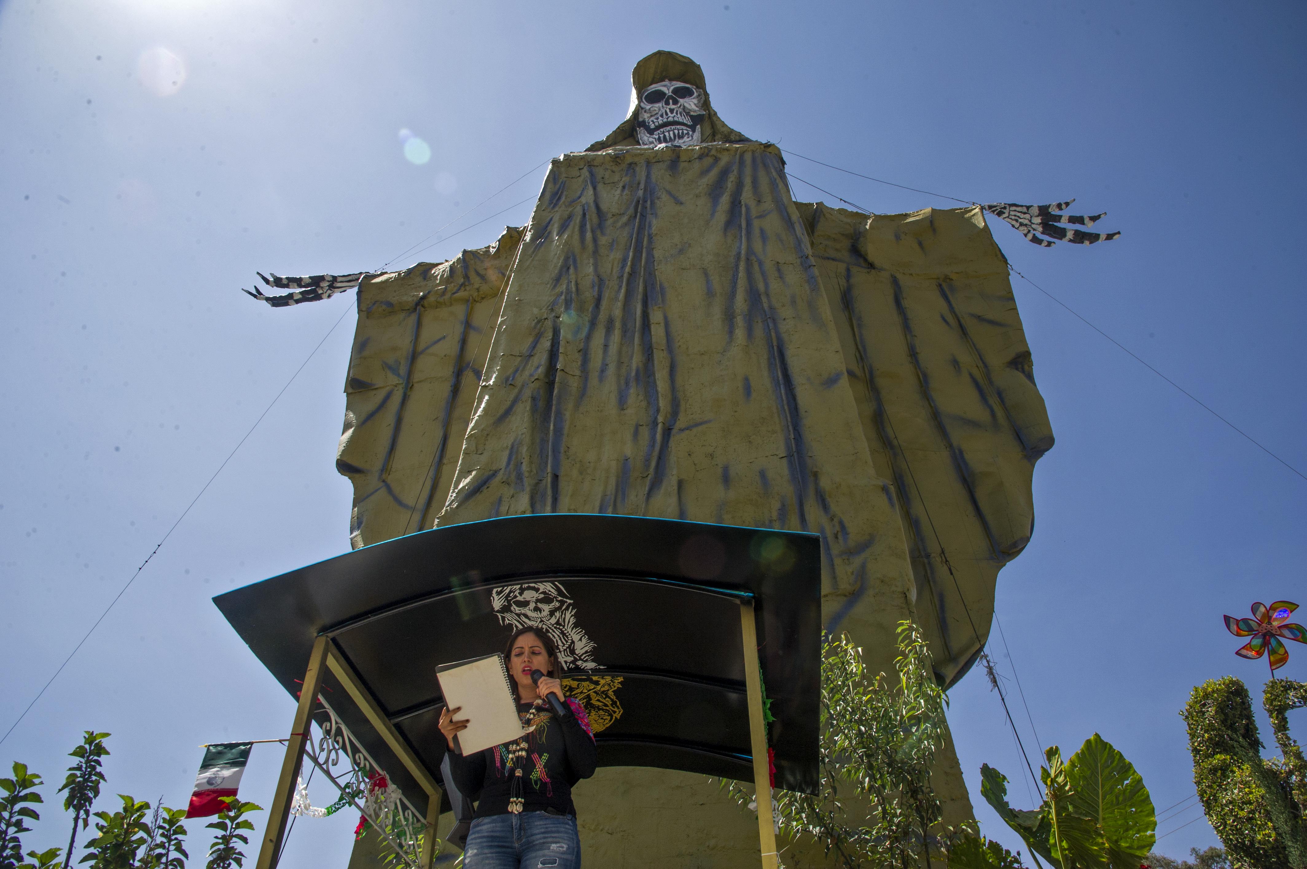 Cristel Legaria, madrina del Santuario Internacional de la Santa Muerte, lee junto a una figura de la santa de 22 metros de altura durante una ceremonia en el municipio de Tultitlán, Estado de México, México, el 4 de octubre de 2020