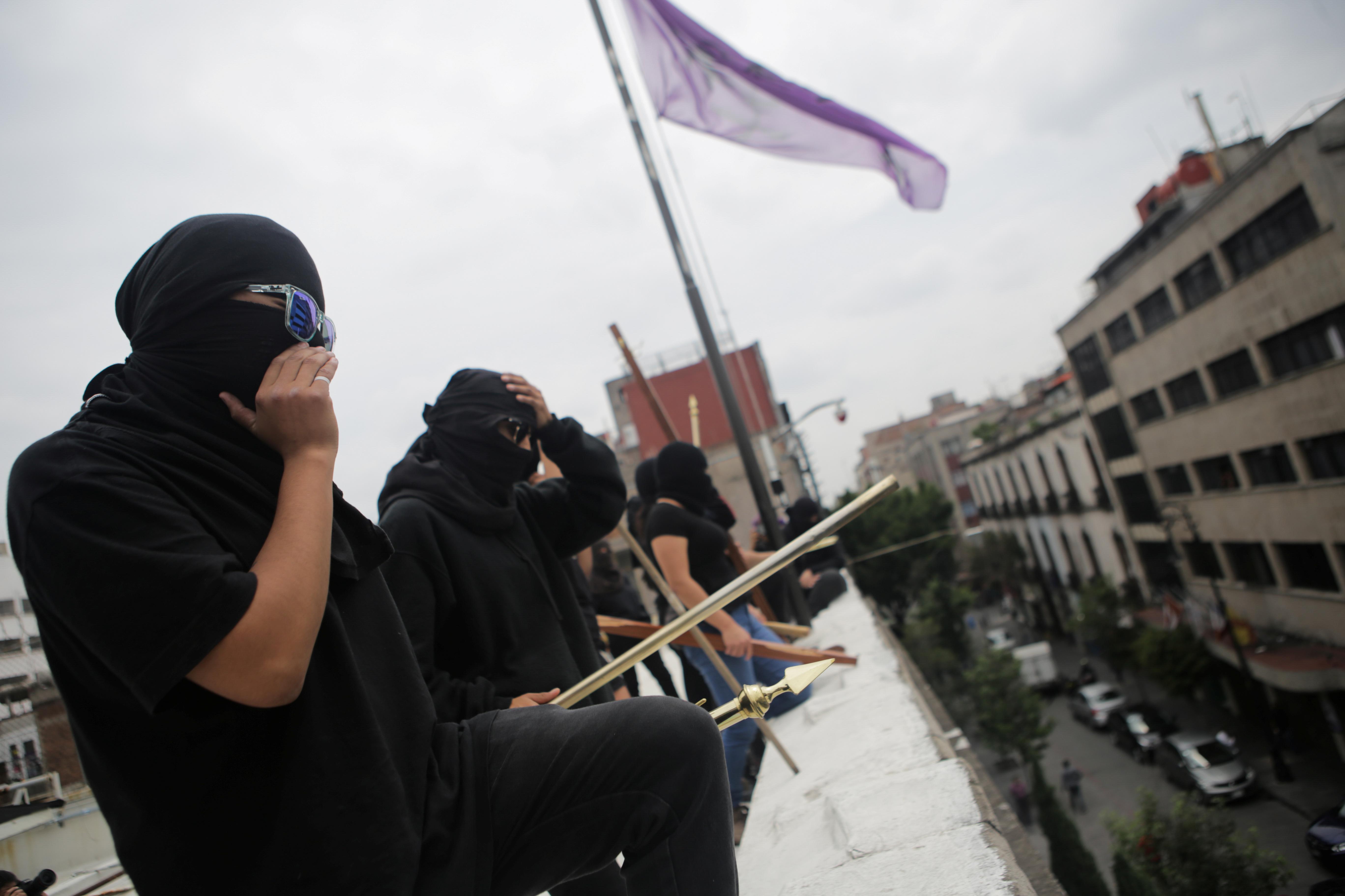 Integrante de un colectivo feminista mira por encima del techo tras ocupar las instalaciones del edificio de la Comisión Nacional de Derechos Humanos, en apoyo a víctimas de violencia de género, México 10 de septiembre de 2020. Foto tomada el 10 de septiembre de 2020.