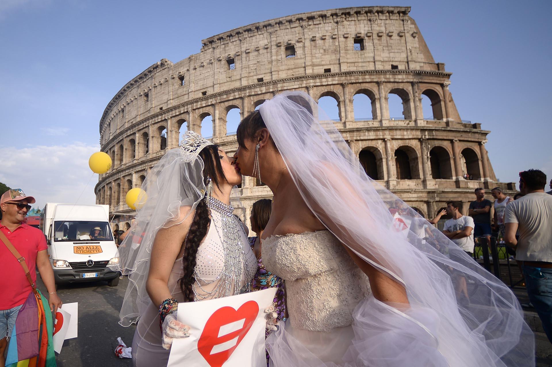 Novias se besan frente al Coliseo en el desfile en Roma el 13 de junio de 2015