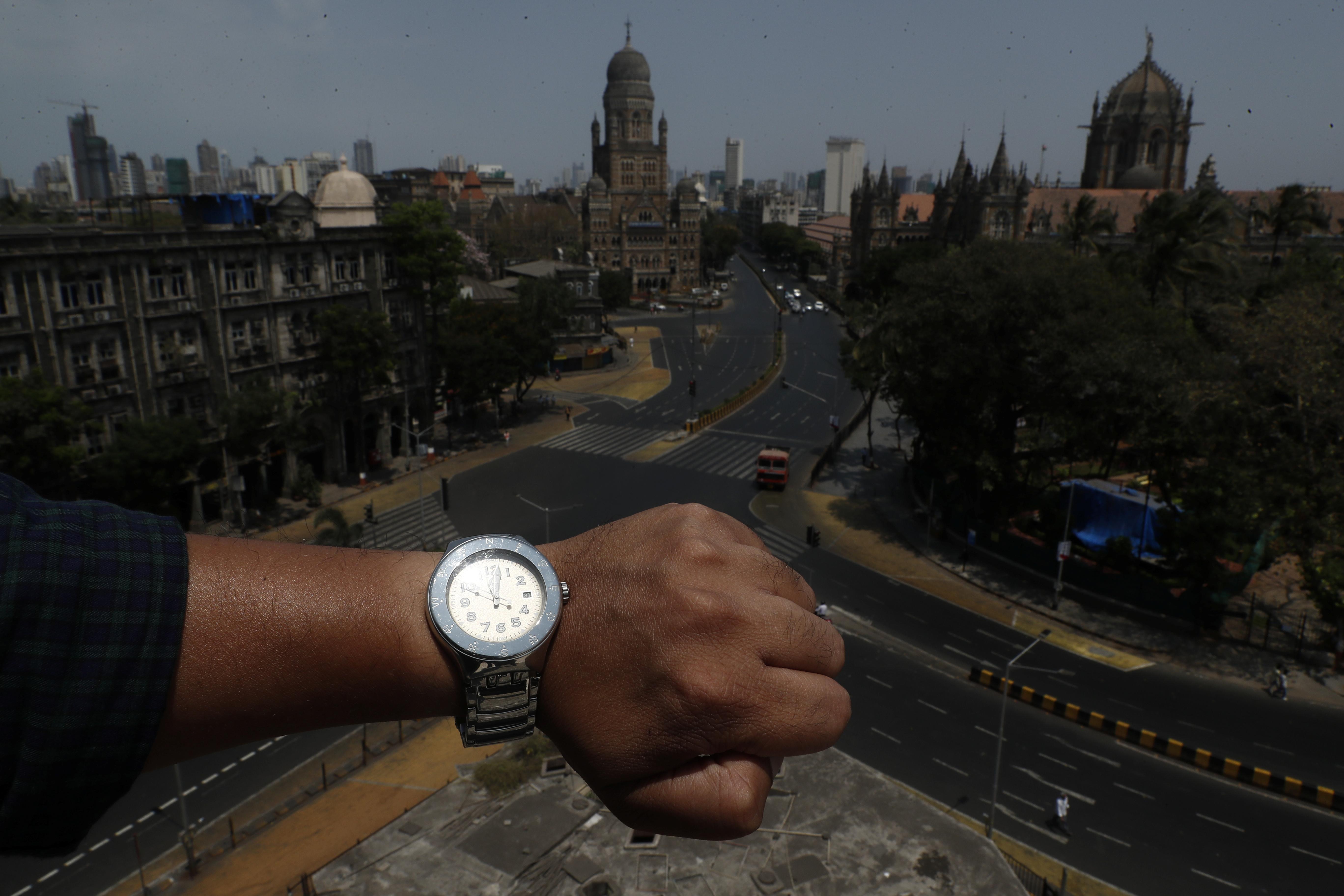 Un fotógrafo muestra en su reloj la hora pico, y la ciudad de Chhatrapati Shivaji Maharaj vacía (REUTERS/Francis Mascarenhas)