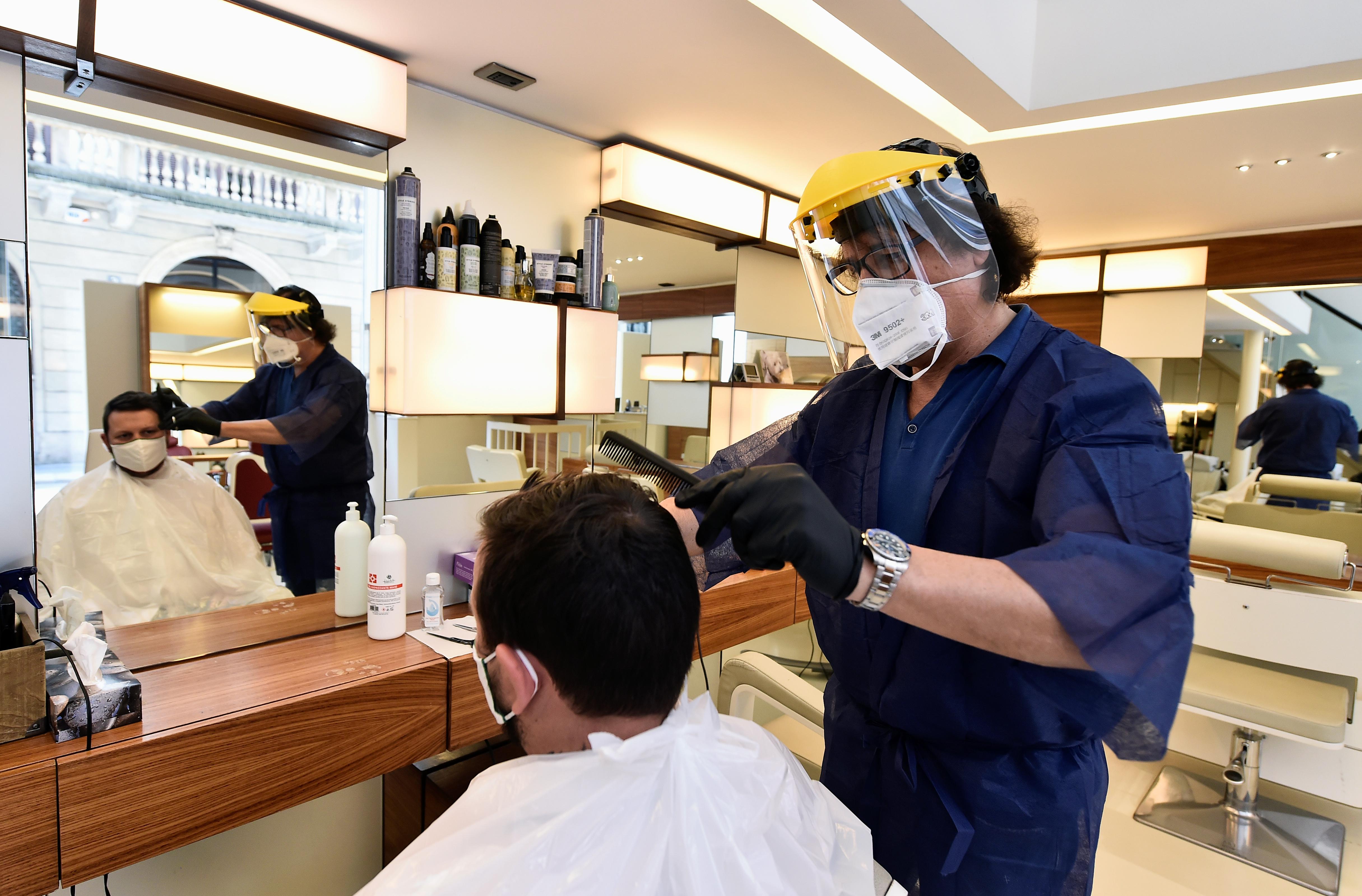 Un empleado corta el cabello de un cliente en Milán (Reuters/ Flavio Lo Scalzo)