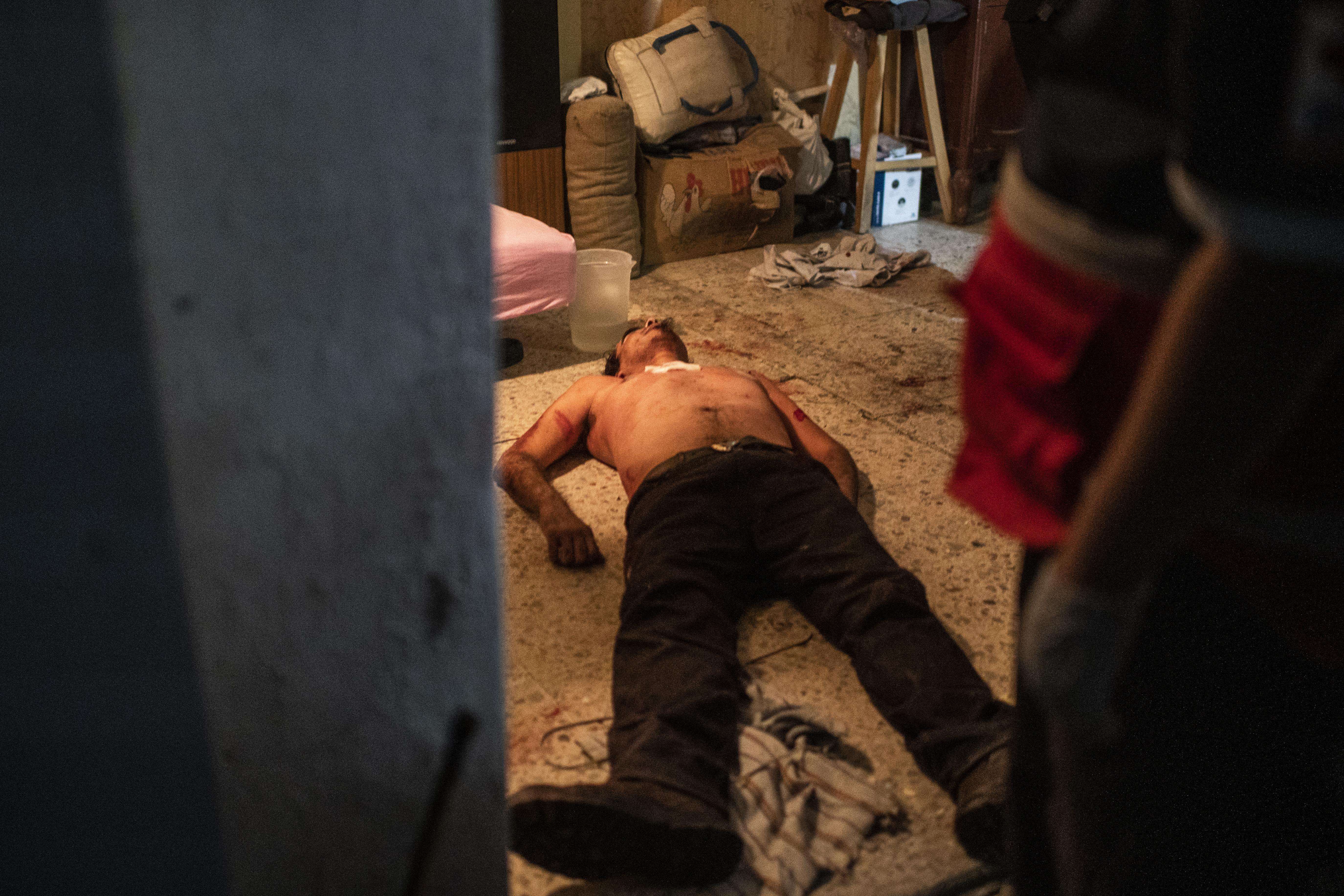 Un hombre que golpeó a su madre e intentó apuñalarse en el pecho, yace en el suelo en Ciudad Nezahualcóyotl, Estado de México, México, el 20 de junio de 2020, durante la nueva pandemia de coronavirus de COVID-19. (Foto por Pedro PARDO / AFP)