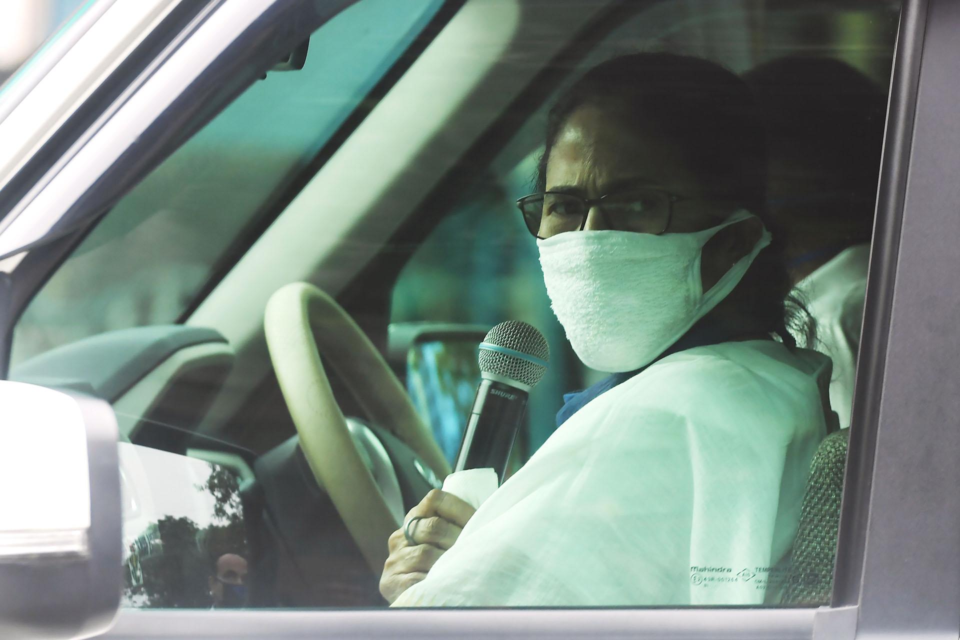 La Ministra Principal de Bengala Occidental, Mamata Banerjee, saluda con la mano mientras pronuncia un discurso desde su coche durante la cuarentena en Calcuta el 23 de abril de 2020. (Foto de Dibyangshu SARKAR / AFP)
