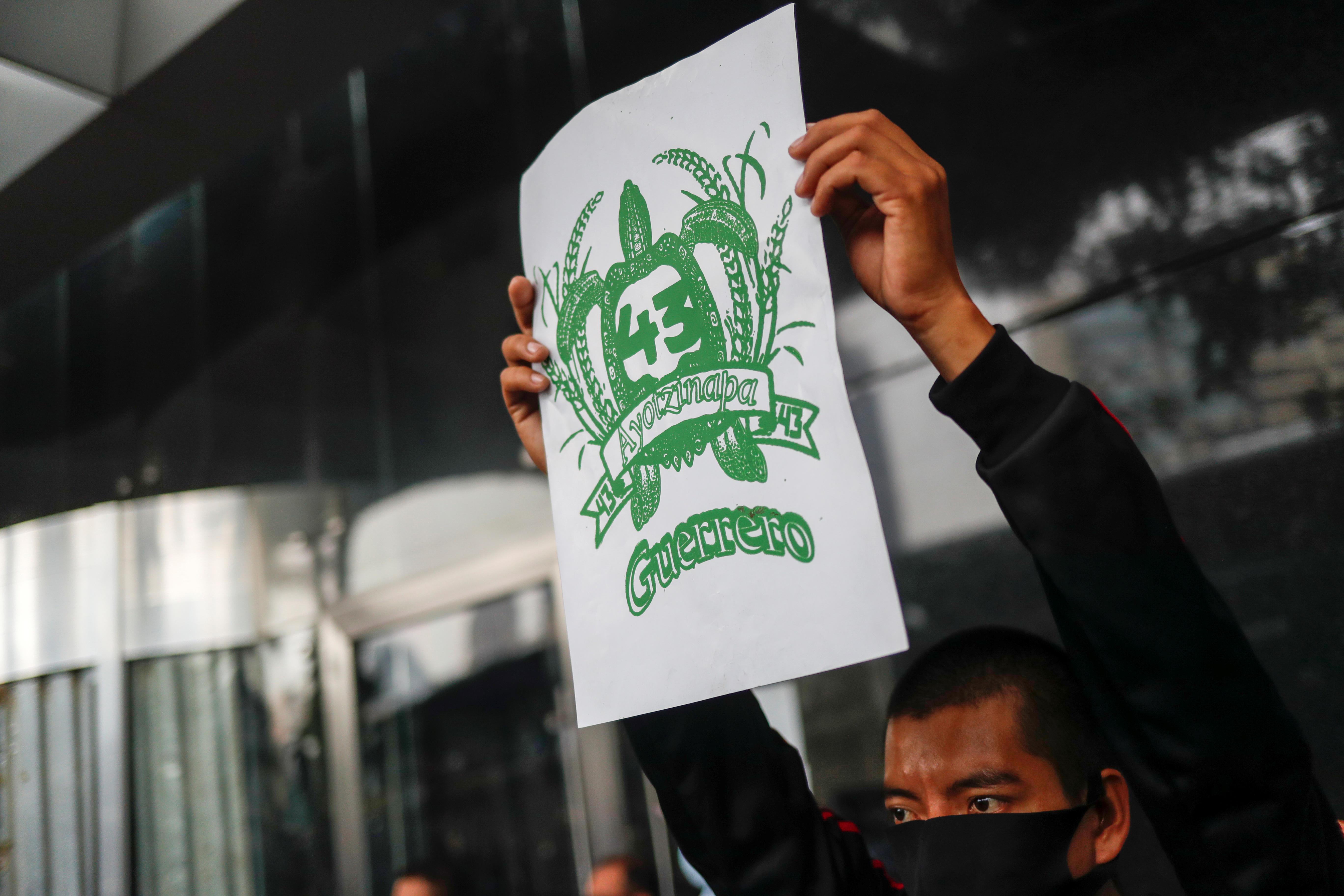 Un estudiante de la EEscuela Normal Rural de Ayotzinapa sostiene un cartel durante una protesta frente a la Fiscalía General, antes del sexto aniversario de la desaparición de 43 estudiantes, en la Ciudad de México, México, 25 de septiembre de 2020.
