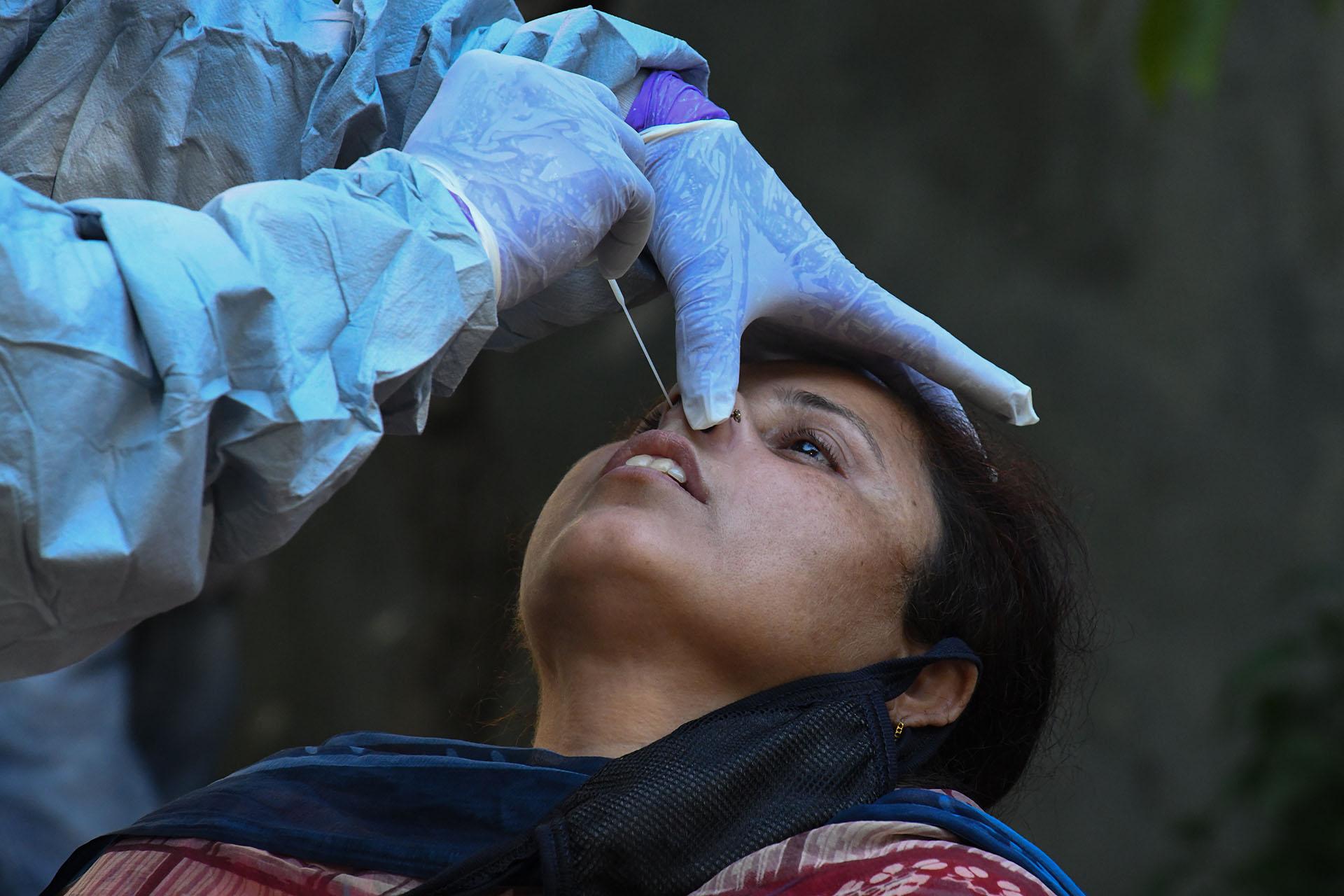 Un médico toma una muestra de una mujer para una prueba de COVID-19 en Amritsar el 23 de abril de 2020, durante la cuarentena nacional impuesta por el gobierno como medida preventiva contra el coronavirus (Foto de NARINDER NANU / AFP)