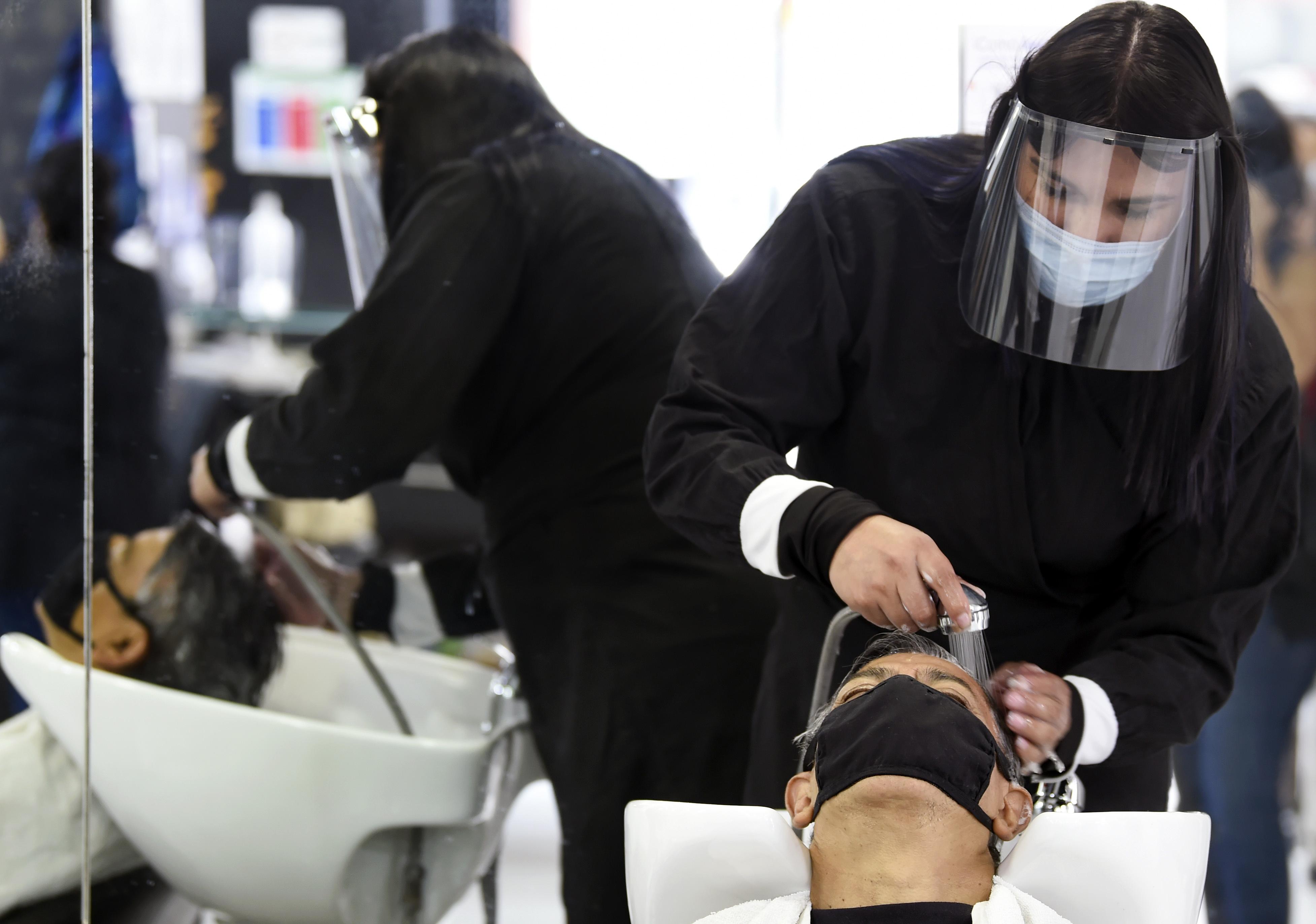 Un empleado en un salón de belleza atiende a un cliente, durante la pandemia COVID-19, en la Ciudad de México el 29 de junio de 2020. (Foto: ALFREDO ESTRELLA / AFP)