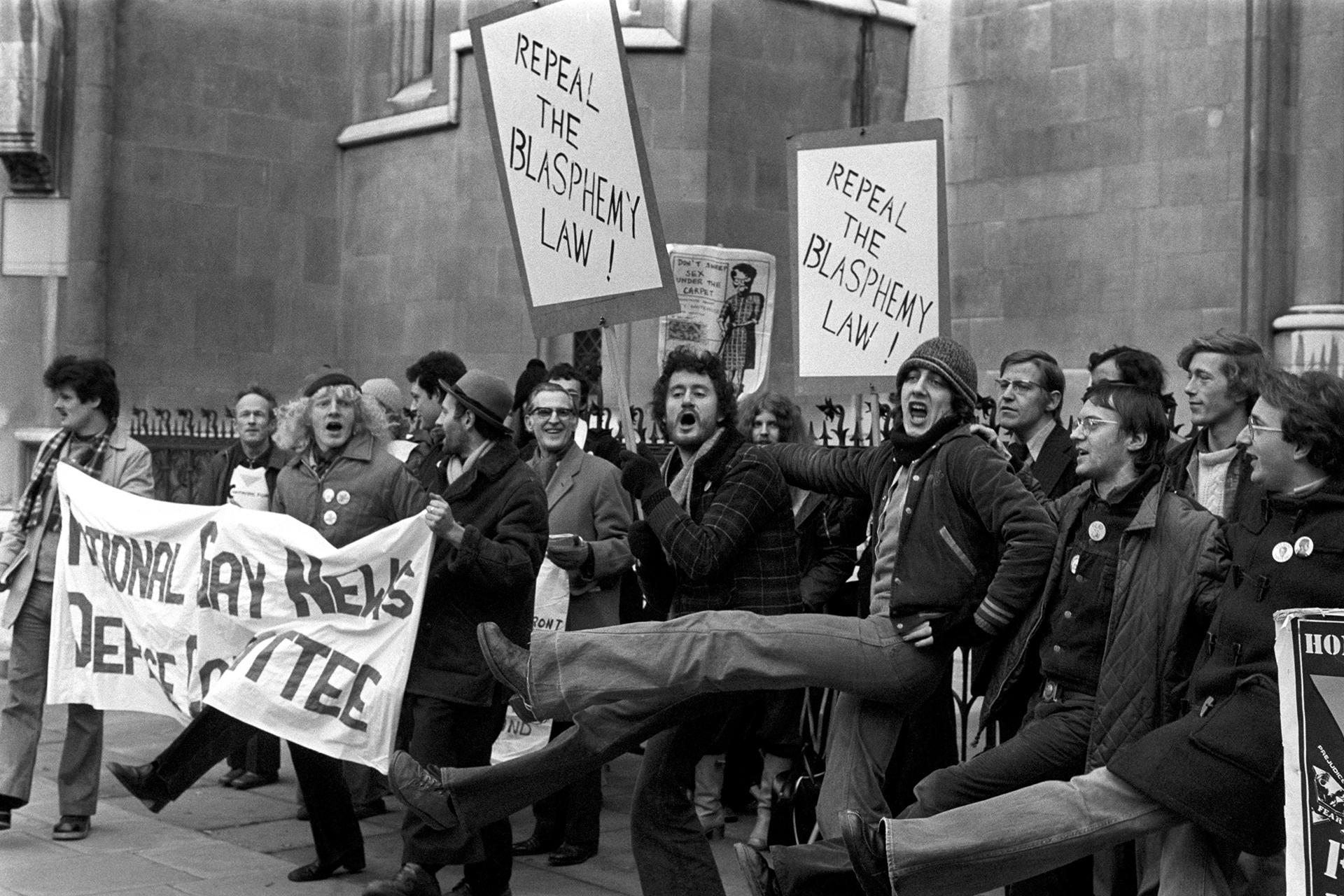 Patadas altas y pancartas desplegadas fuera de los Tribunales de Justicia, Strand, Londres, durante una manifestación de los partidarios del periódico Gay News en 1978.