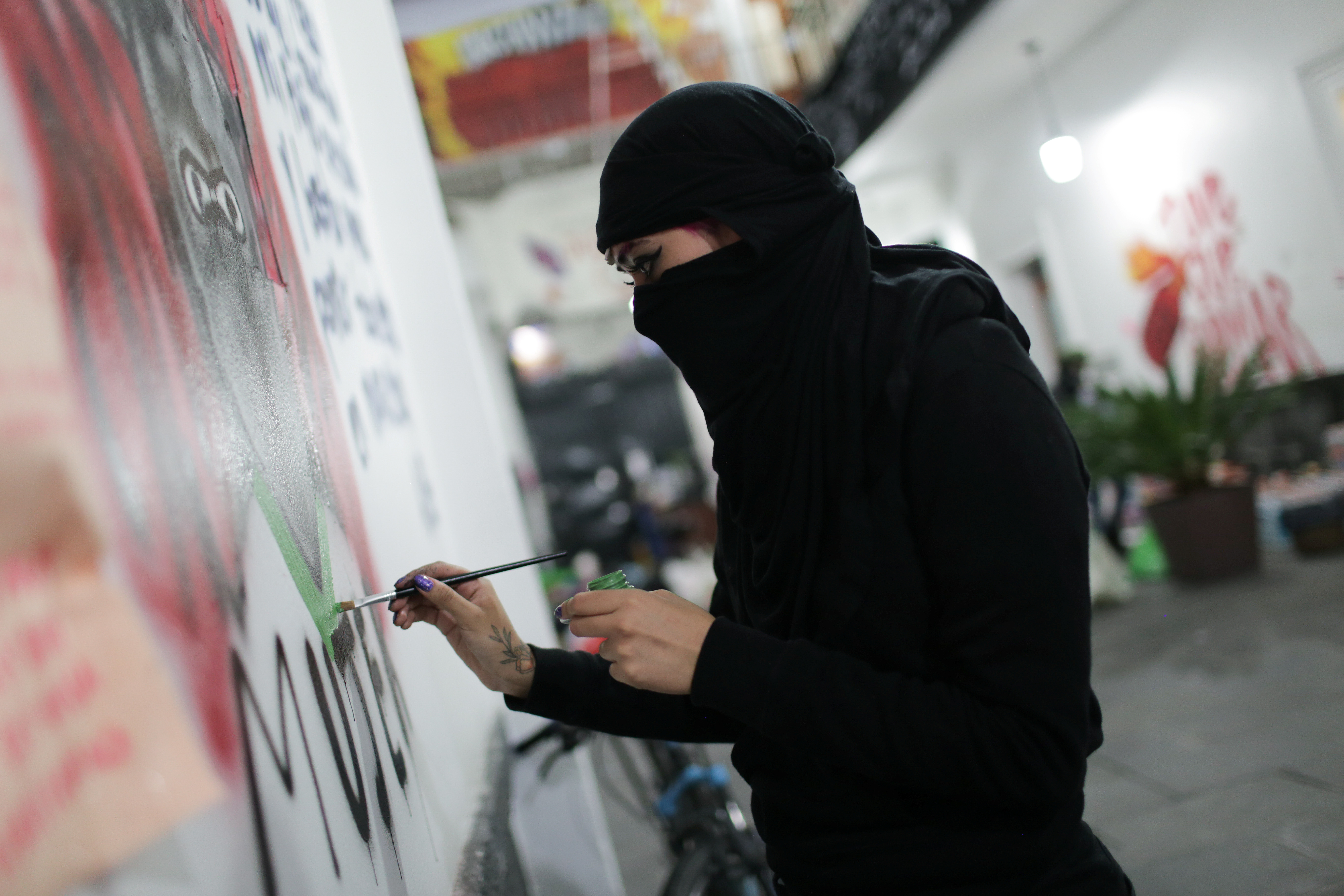 Una integrante de un colectivo feminista pinta un graffiti dentro de las instalaciones del edificio de la Comisión Nacional de Derechos Humanos, en apoyo a las víctimas de violencia de género, en la Ciudad de México, México, 10 de septiembre de 2020. Fotografía tomada el 10 de septiembre de 2020.