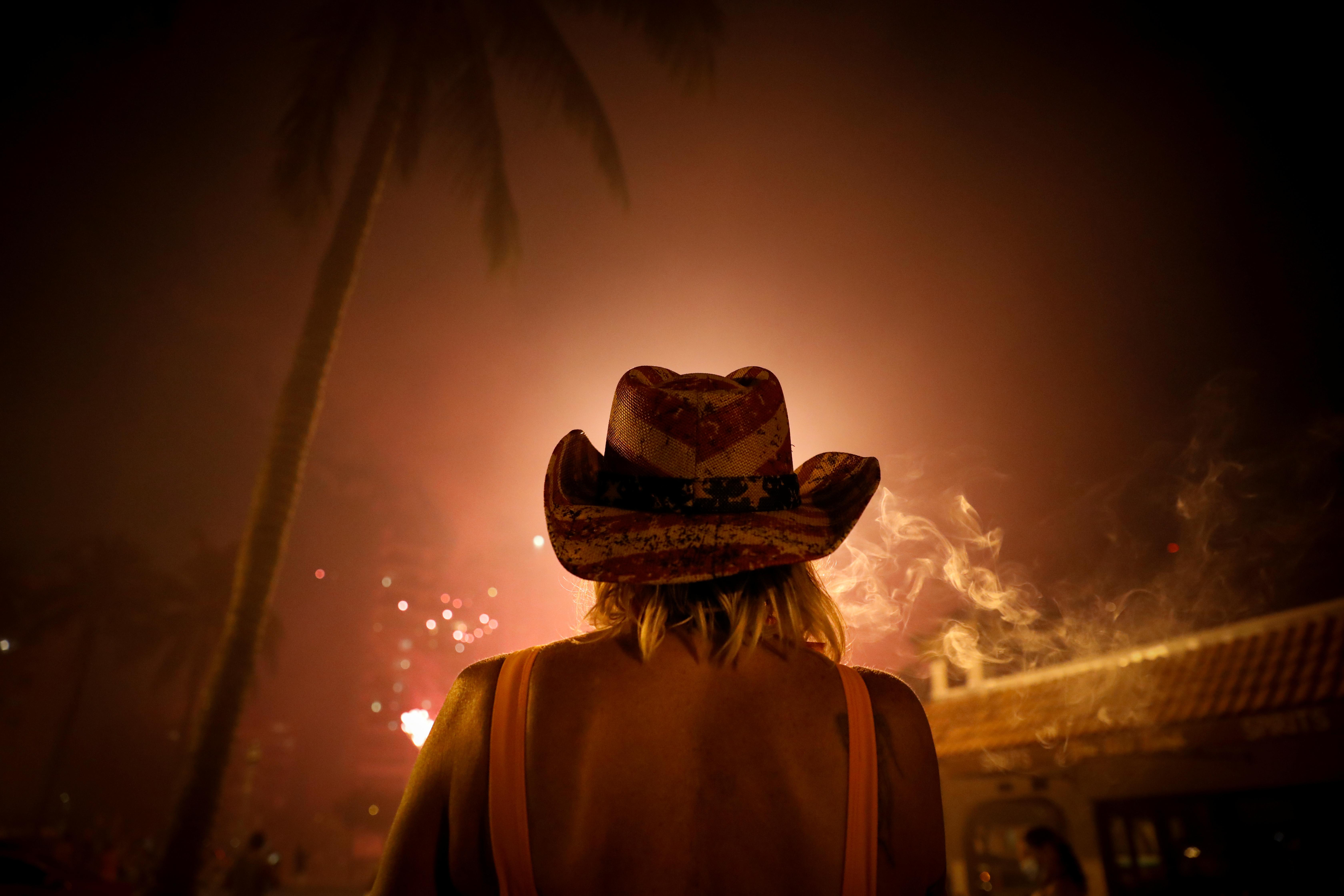 Una mujer mira los fuegos artificiales